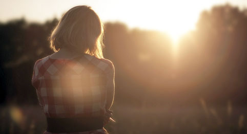 girl standing in a field looking out at the sun rays