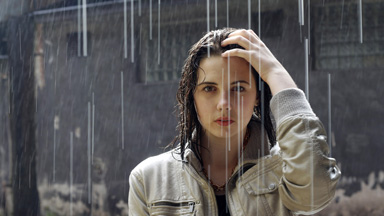 woman standing in rain getting wet