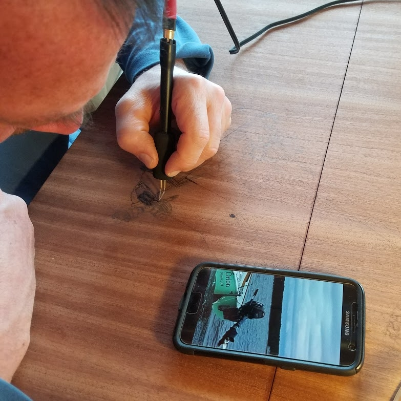 Getting the details of the outboard motor just right by looking at a photo of ORION on his phone.