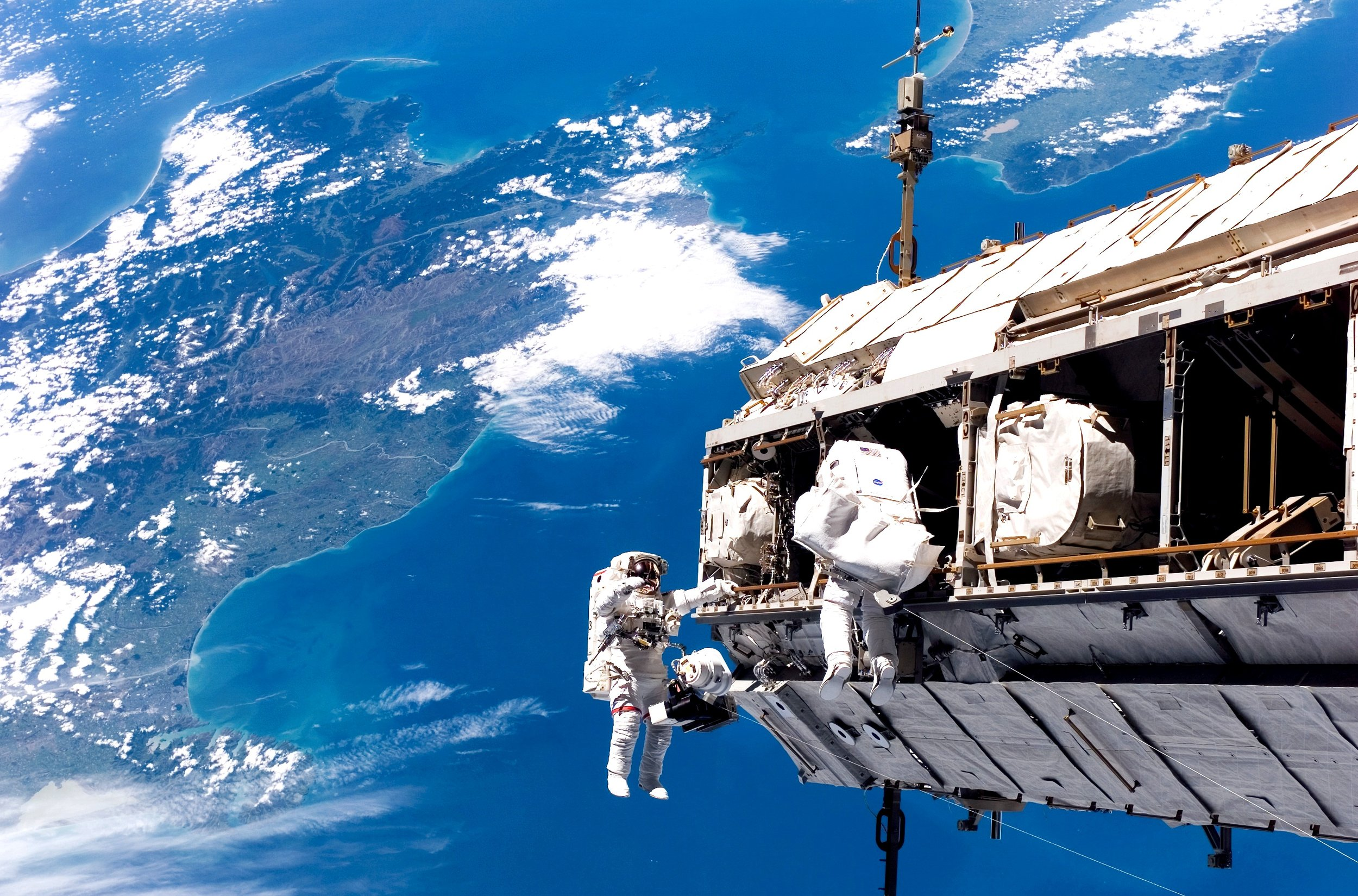 U.S. astronaut Robert Curbeam (left) and Swedish Astronaut Christer Fuglesang rewire the Station's electrical system in December 2006. The land mass below is New Zealand. Photo credit: NASA.