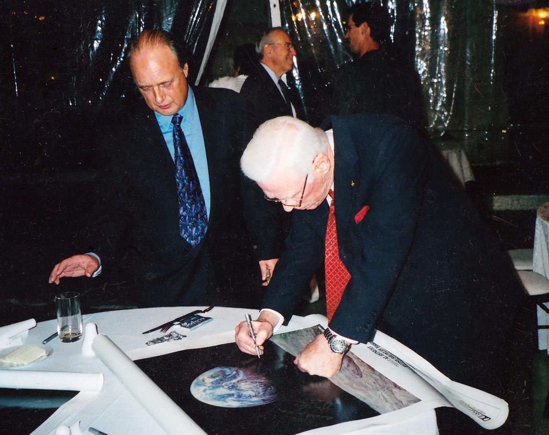 Astronaut Gene Cernan, the last man to walk on the moon, signs a  For All Mankind  poster with filmmaker Al Reinert.  Photo Courtesy Al Reinert