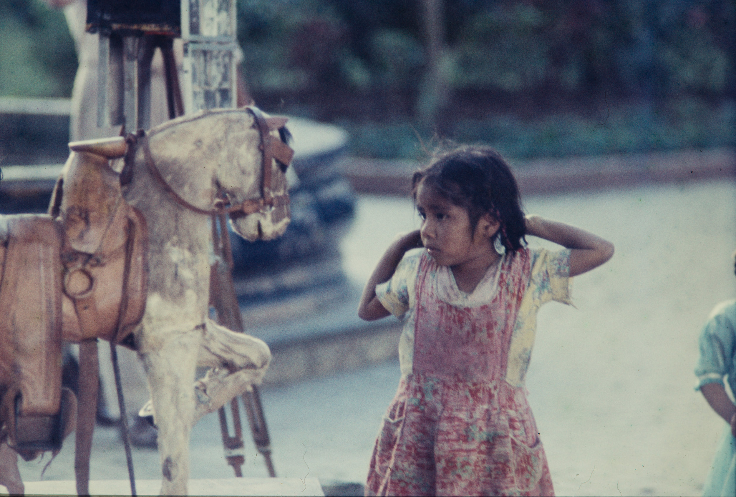 Young girl looking at toy horse, Mexico, 1957