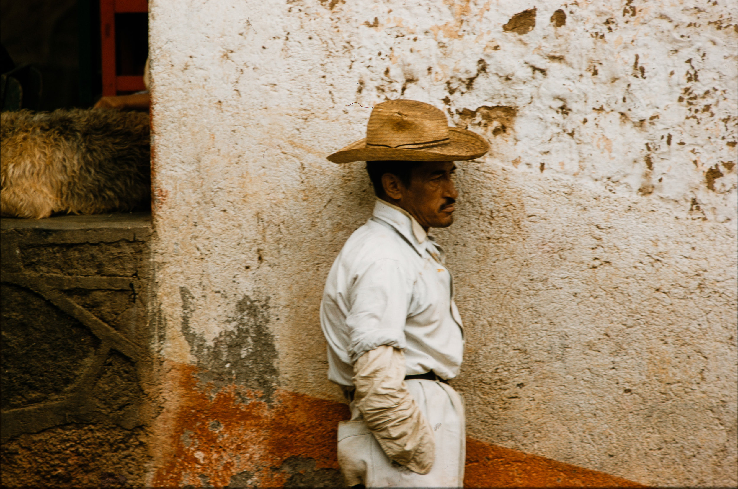 Man with straw hat against wall, Mexico, 1957