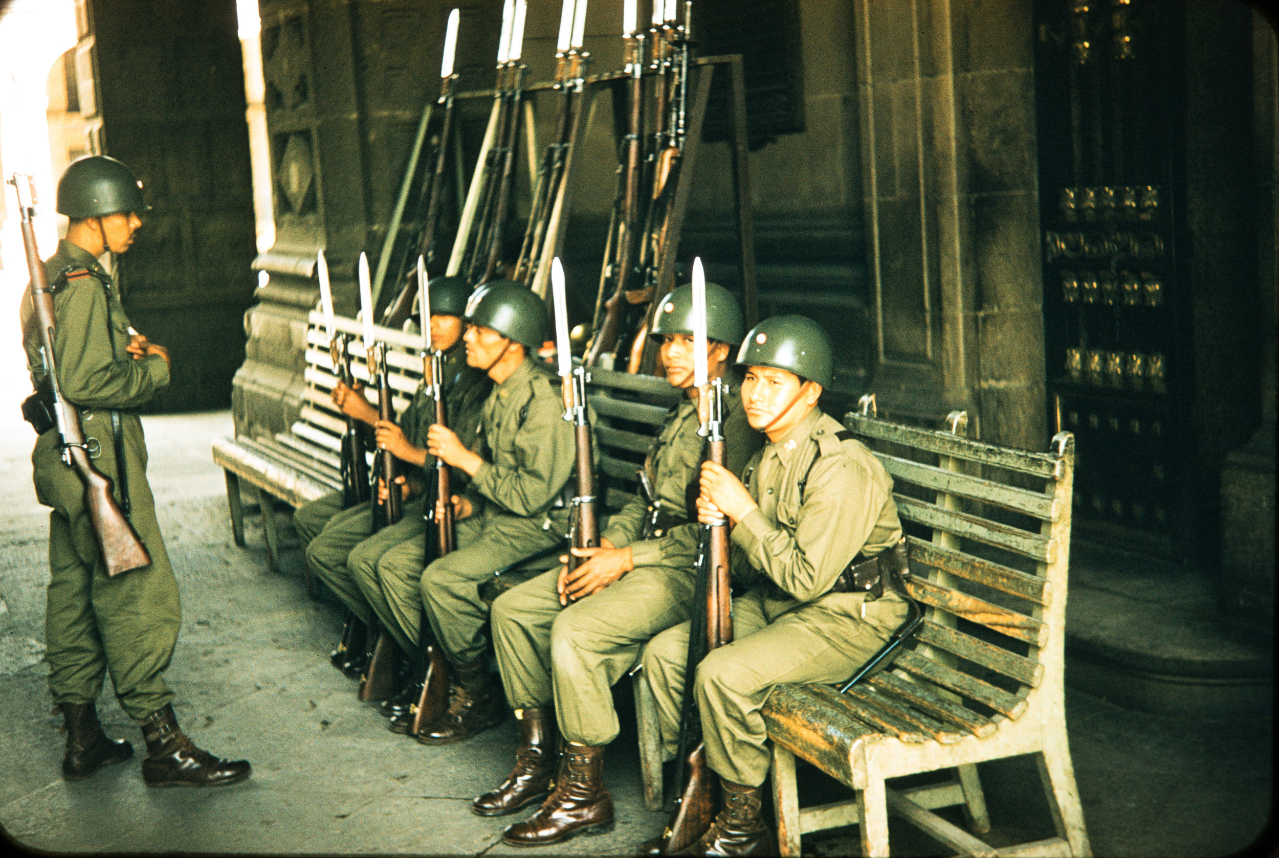 Seated officials with guns, Mexico, 1957