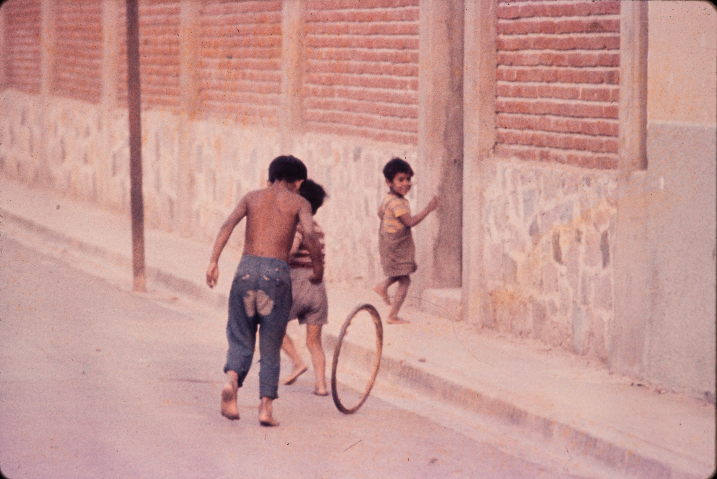 Boys playing with wheel, Mexico, 1957