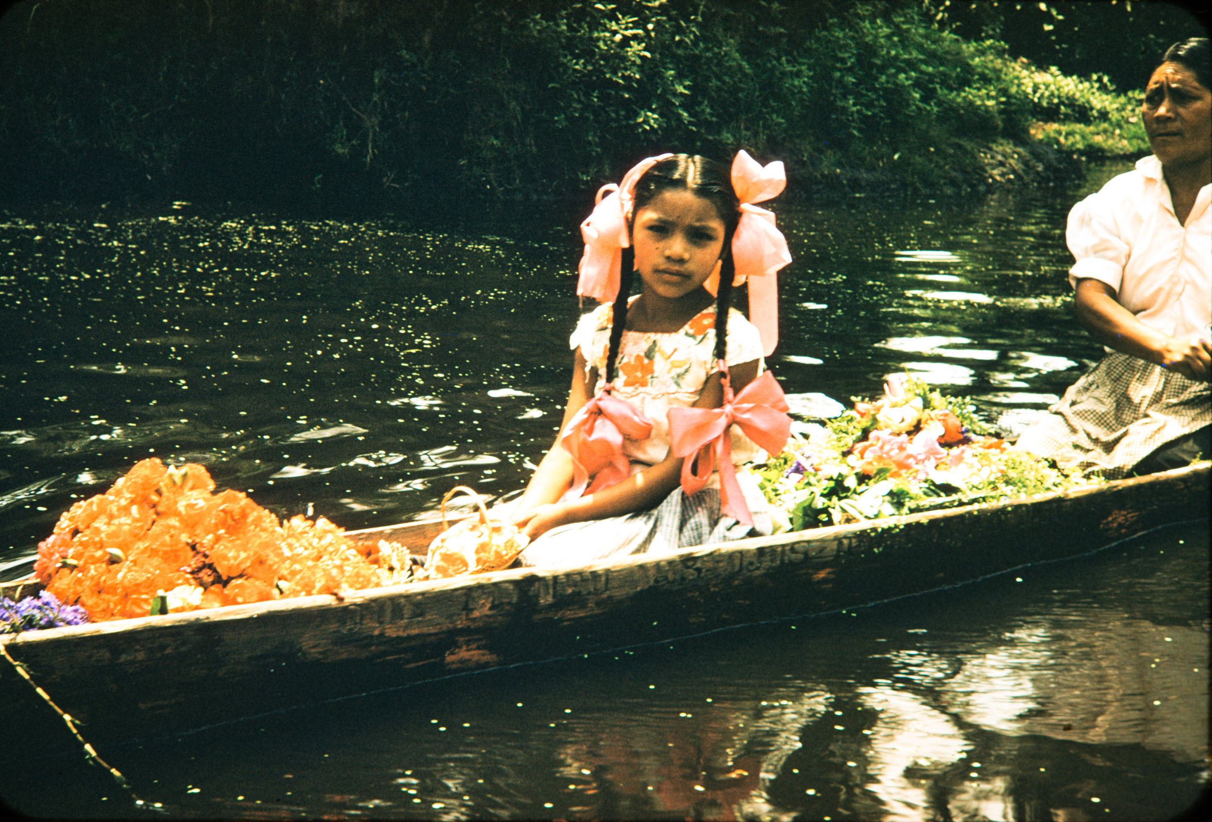 Girl with pink ribbons in canoe, Mexico, 1957