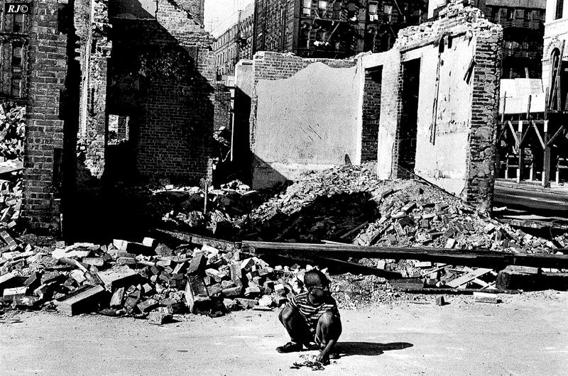 Young boy sitting in wreckage, Harlem, 1953