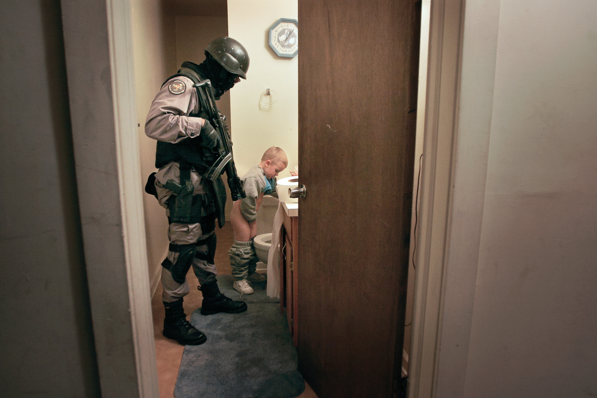 After a drug raid in 2005, a member of the Durham Police Department Selective Enforcement Team escorts a child to the bathroom. His mother was temporarily detained during the search of the home and couldn't tend to him. Through raids, officers hope to recover illegal or stolen guns, and disrupt drug trafficking and gang activity. Some residents welcome the raids; others complain that they terrorize the neighborhood, and that police efforts should focus on solving murders and other violent crimes. Many SET officers have children, and none of them like it when kids are caught in the middle of drug raids.
