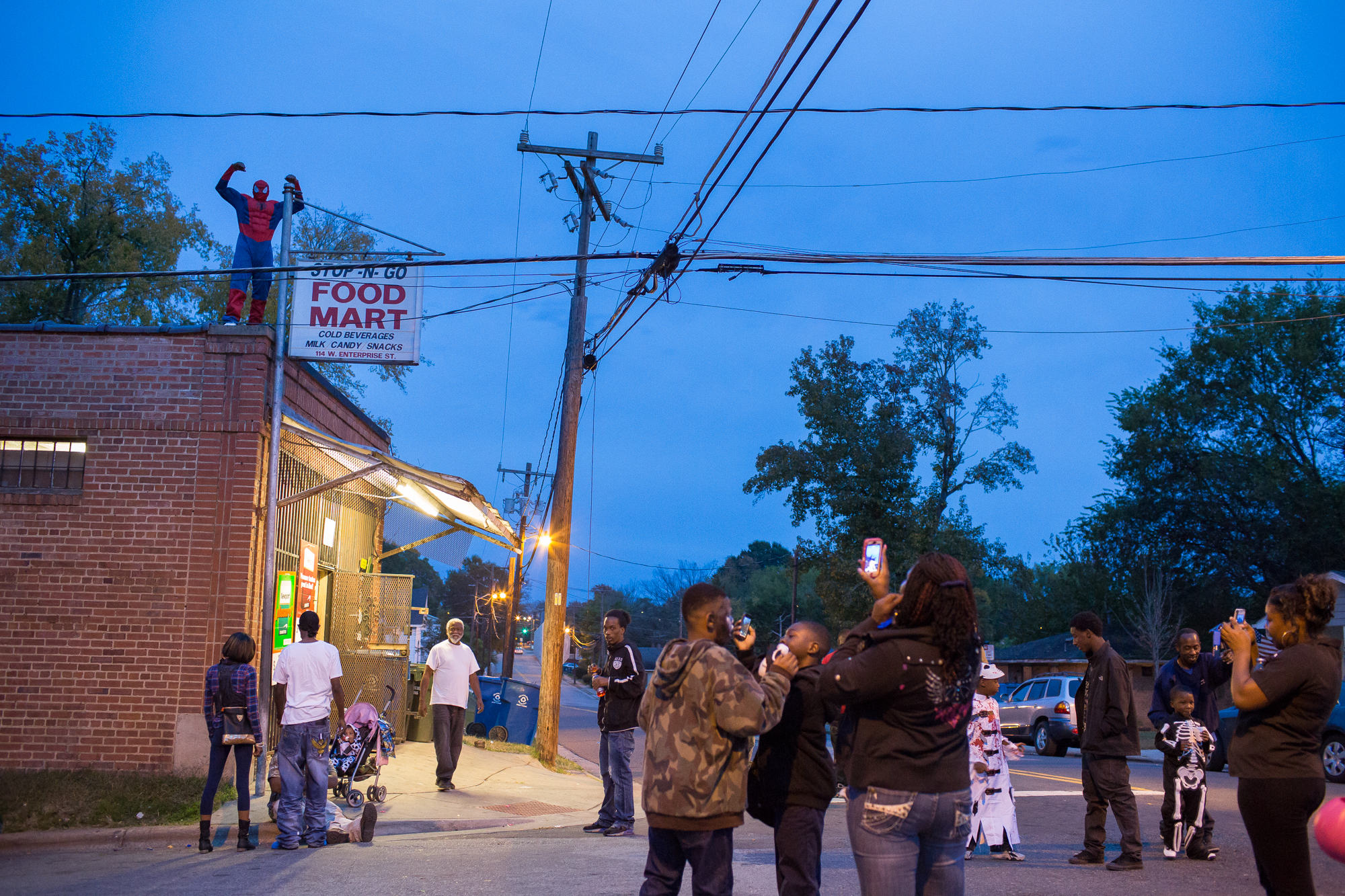 """A man who calls himself """"Lil' Salt"""" flexes in triumph after climbing the corner store dressed as Spider-Man during Halloween festivities in Durham's Southside neighborhood. The Southside has endured despite violence in the past decade, but is changing rapidly under the City of Durham's redevelopment plans."""