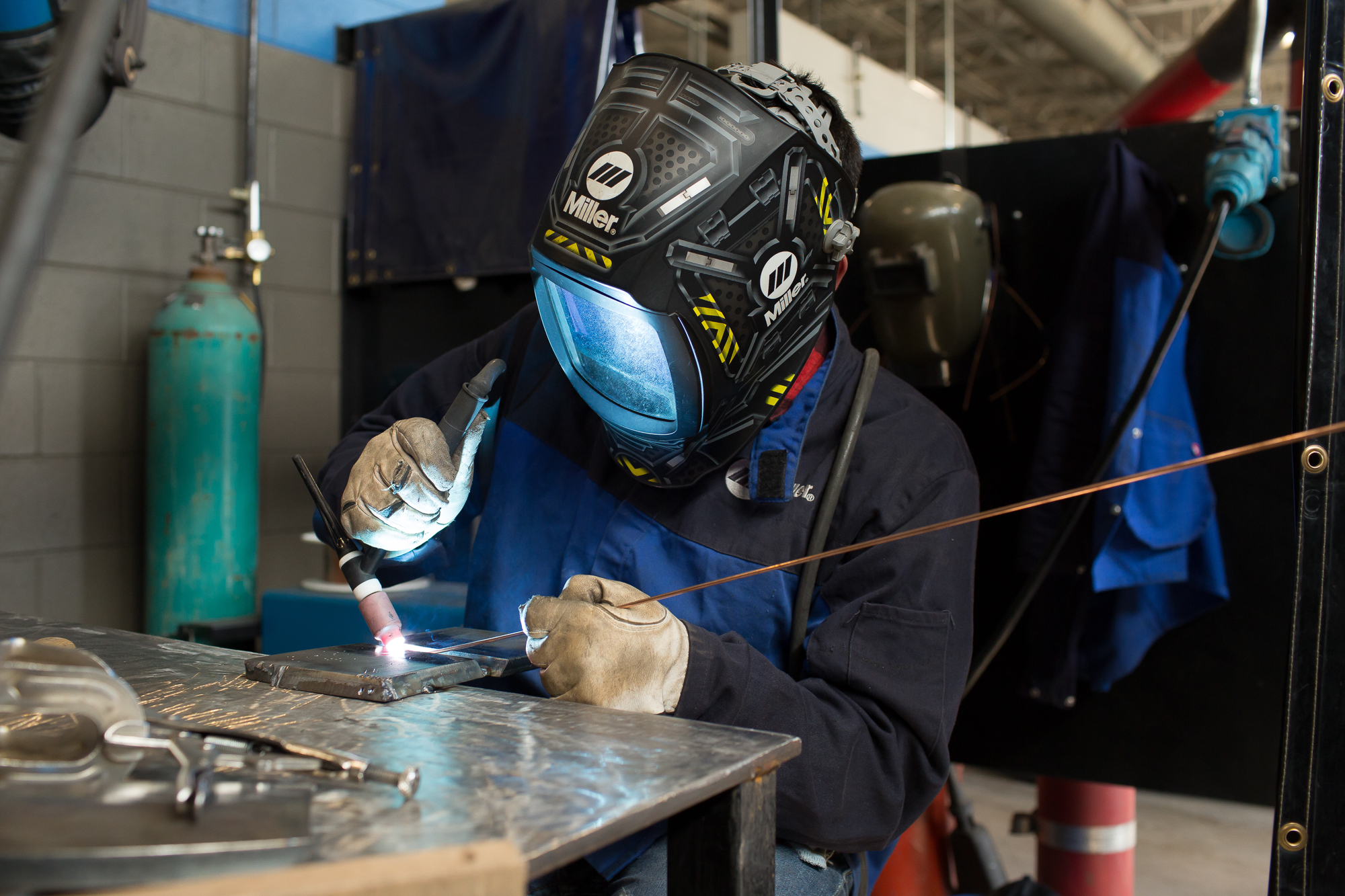 Central Surry High junior Cesar Landeros welds metal plates together during a class assignment at Surry Community College.