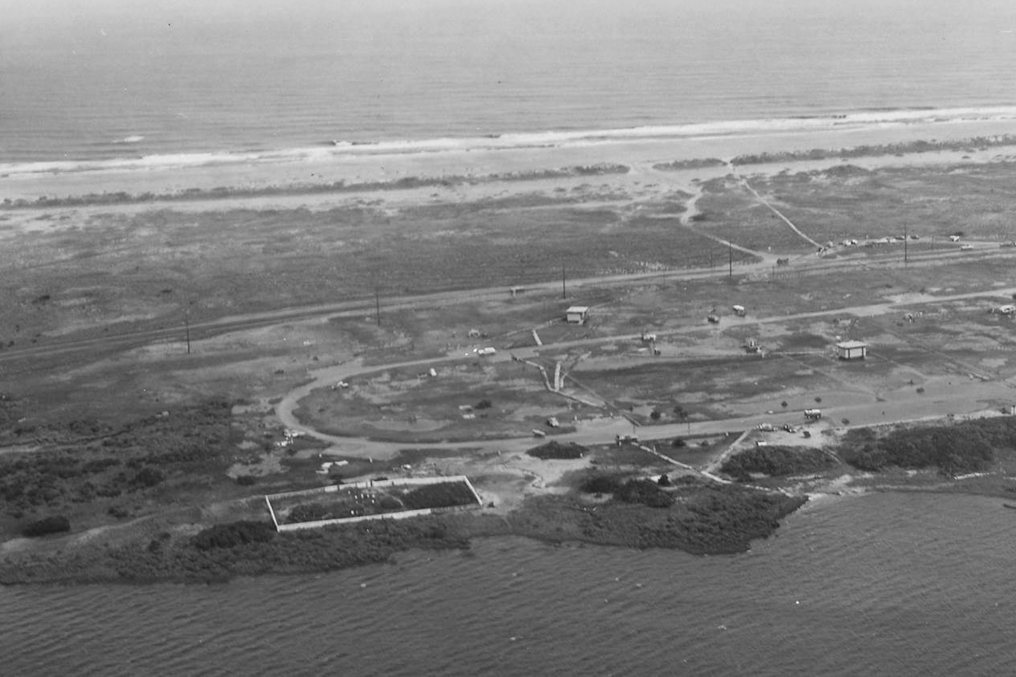 The Salvo Community Cemetery in 1970, with a complete fence and a shoreline with vegetation.  Courtesy of National Park Service, Cape Hatteras National Seashore