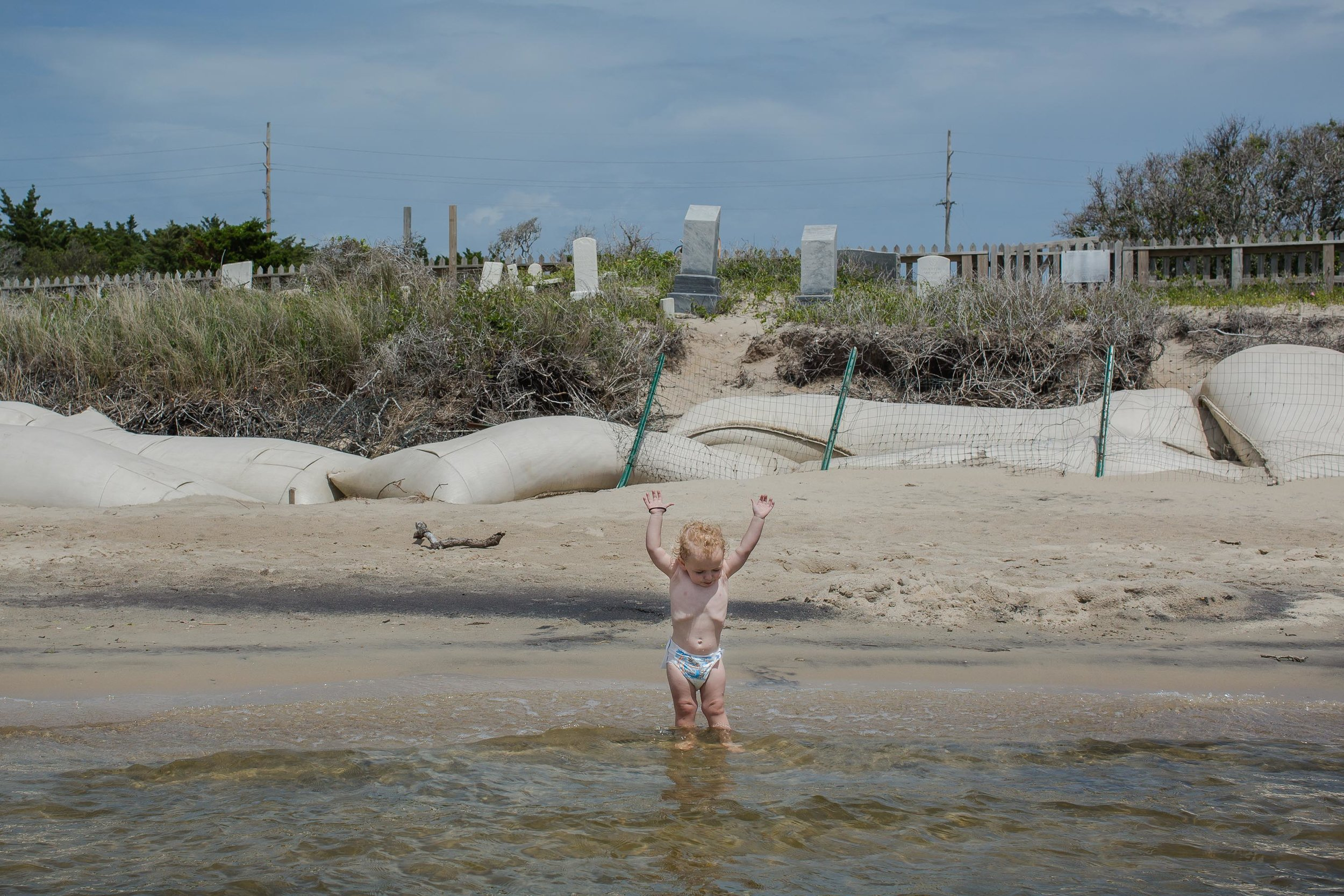 Kaine, 2, plays in the sound near sandbags installed to break waves during storms and slow erosion in the cemetery. May 2018.