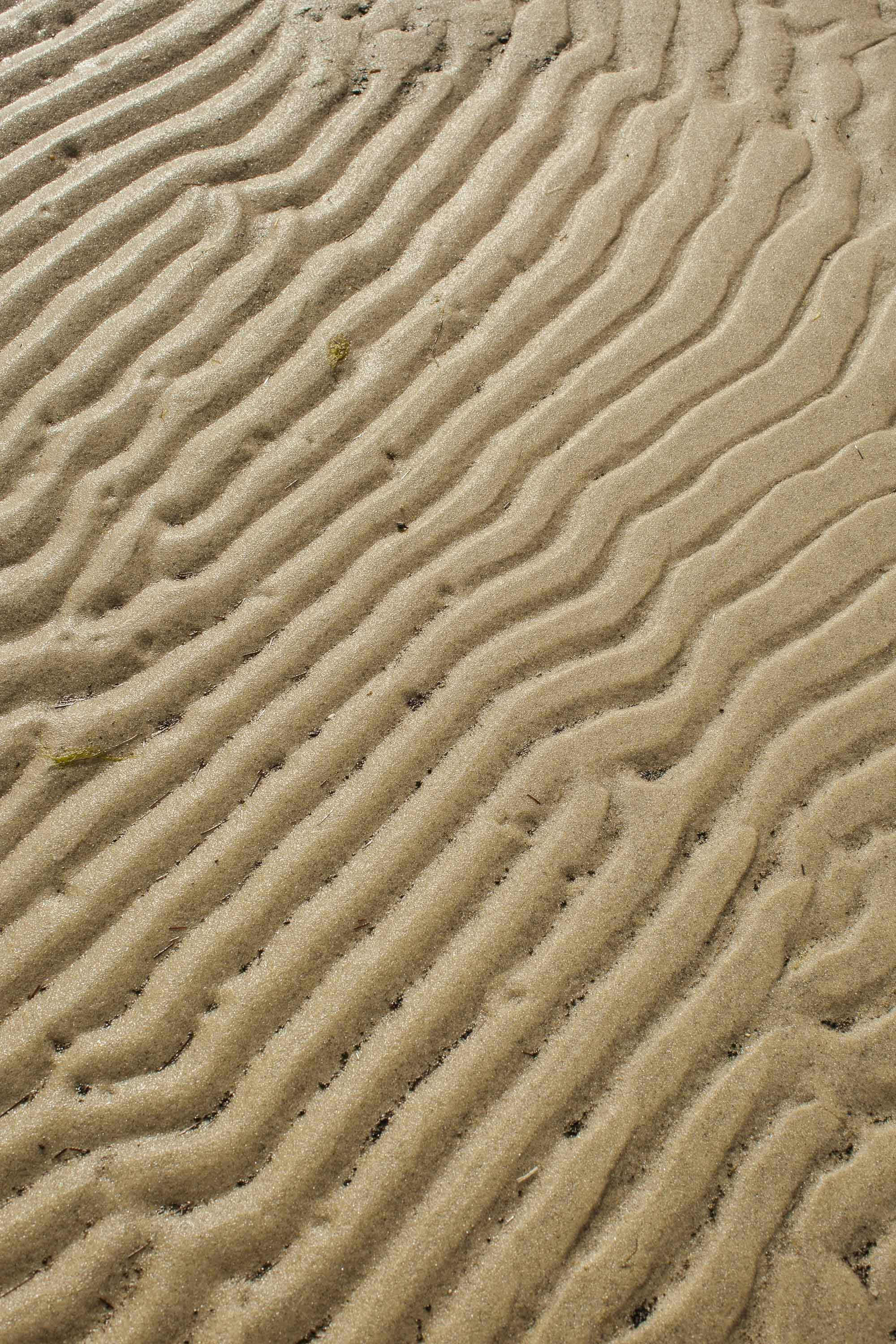 Ripples in the sand left by wave action are visible at low tide.