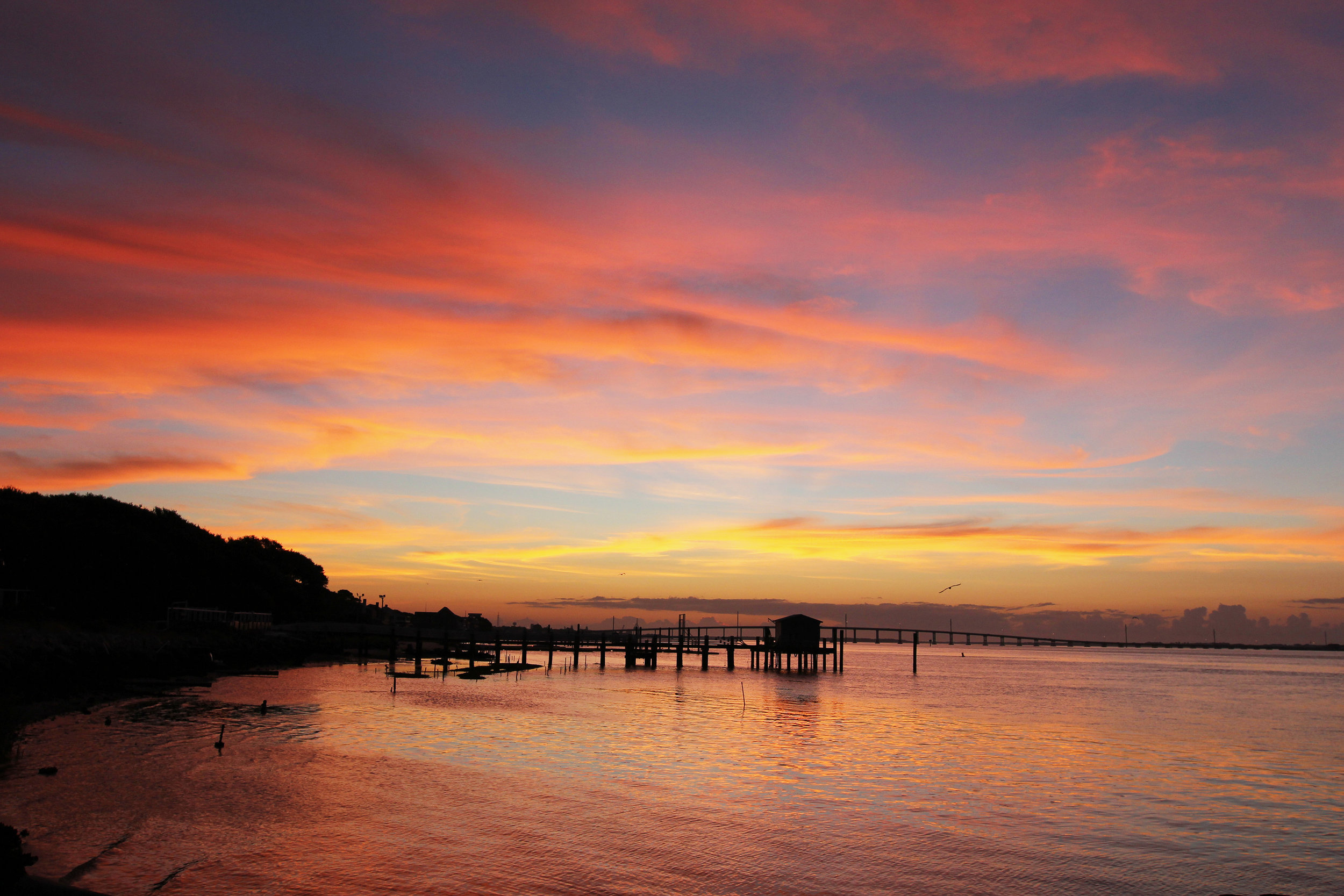 Bogue Sound reflects a cotton candy sky just before the sun rises in Morehead City, NC.