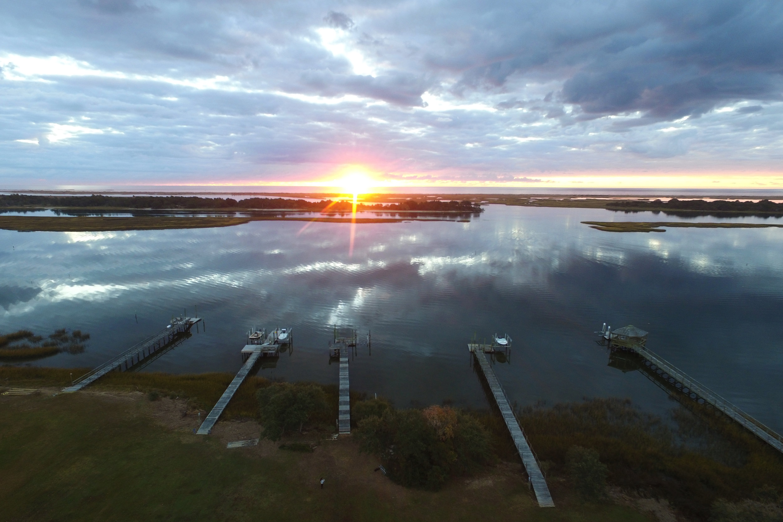The sun rises over Masonboro Island and Masonboro Sound in Wilmington, NC. On the other side of the marsh and barrier island is the Atlantic Ocean.