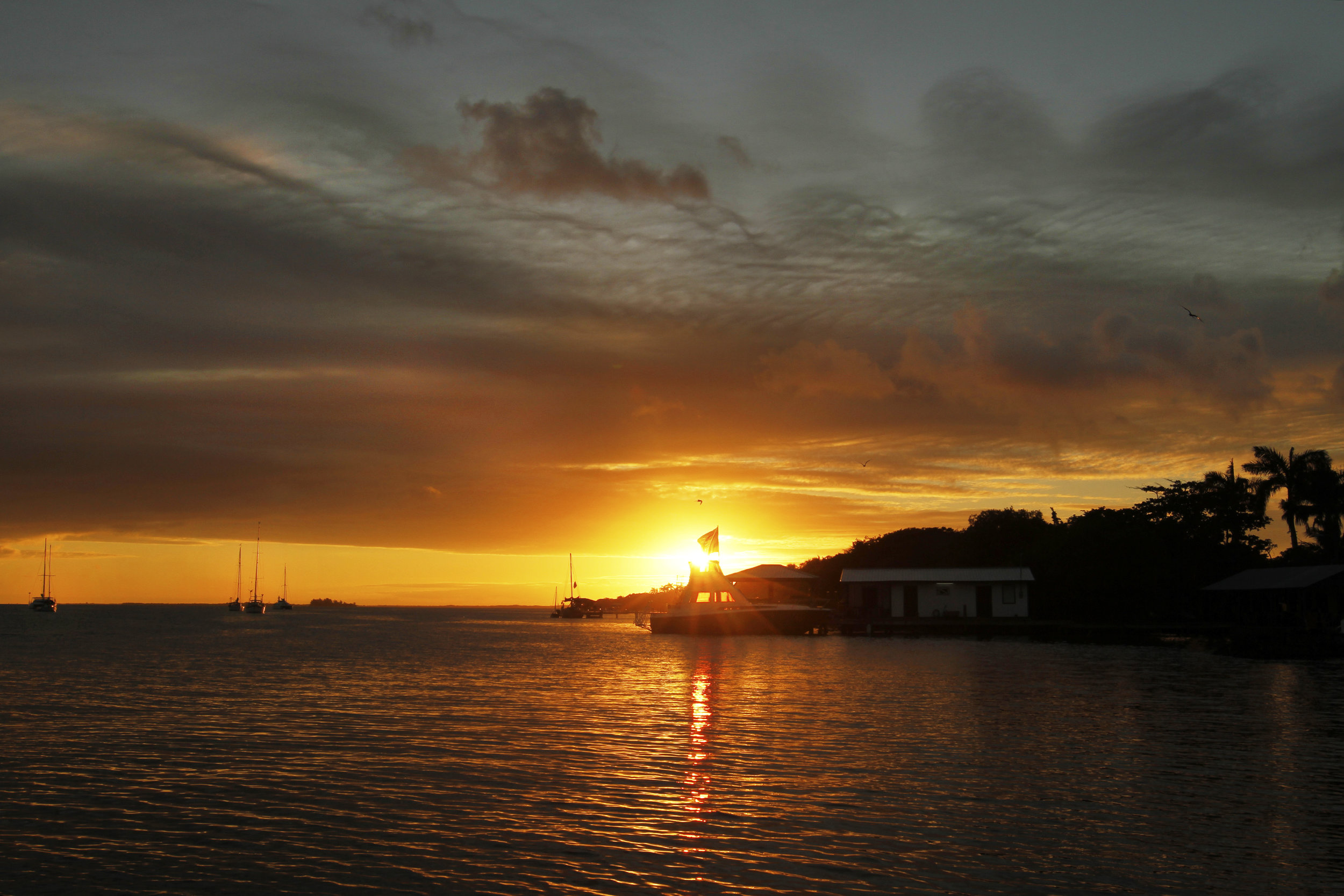 A striking sunset fills the sky over the Placencia Peninsula.