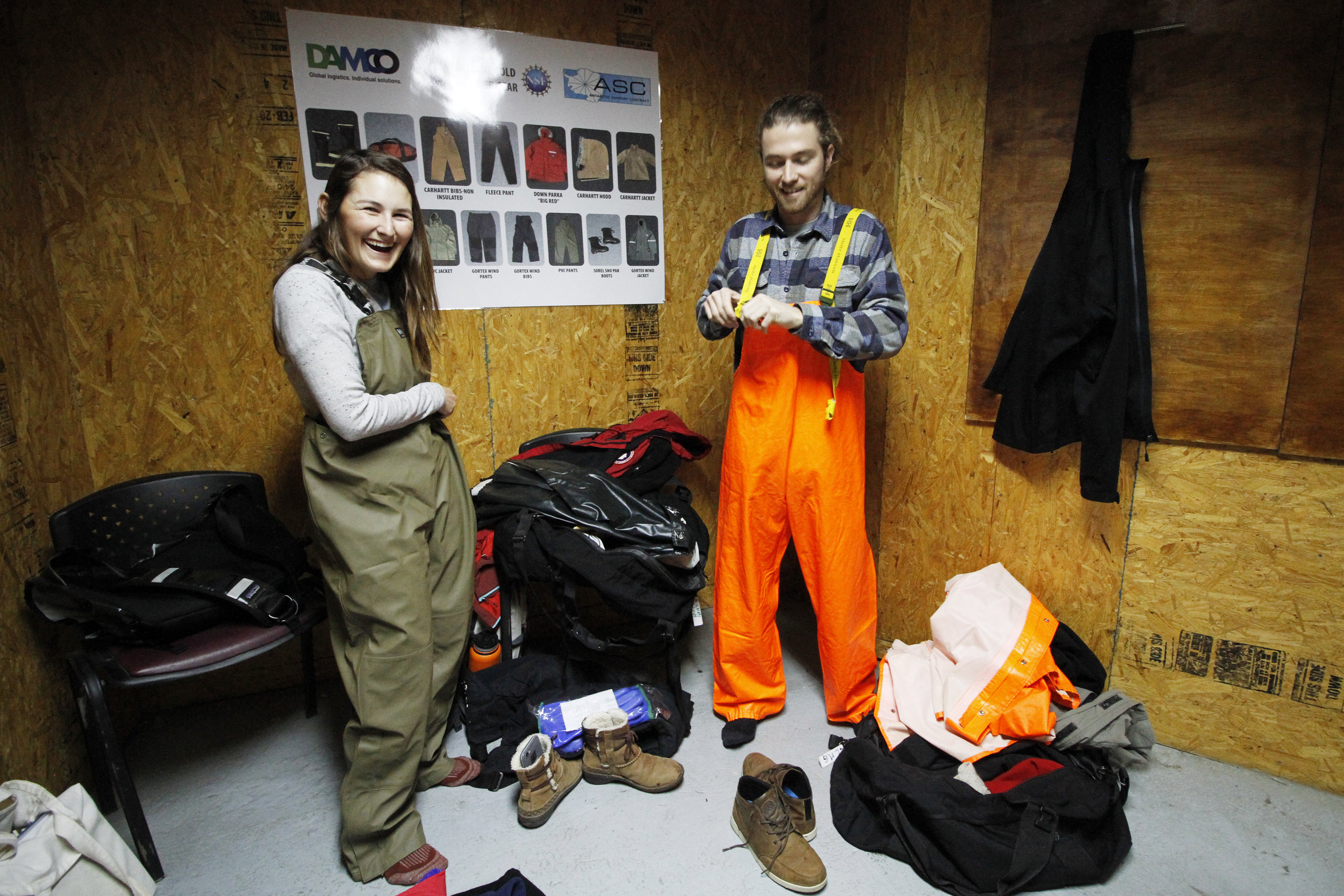 Emma and KC laugh as they don their rain gear — essential for the cold, wet conditions in the Antarctic Peninsula.