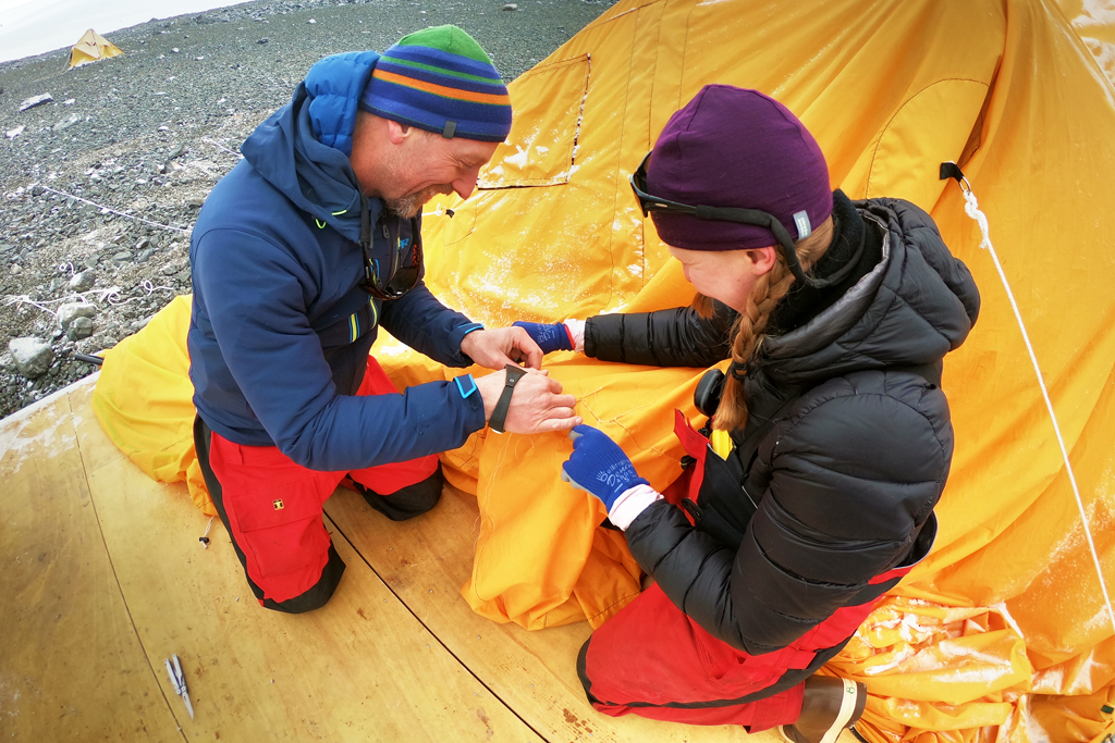 Eric and Amy work together to sew the hole in the kitchen tent.