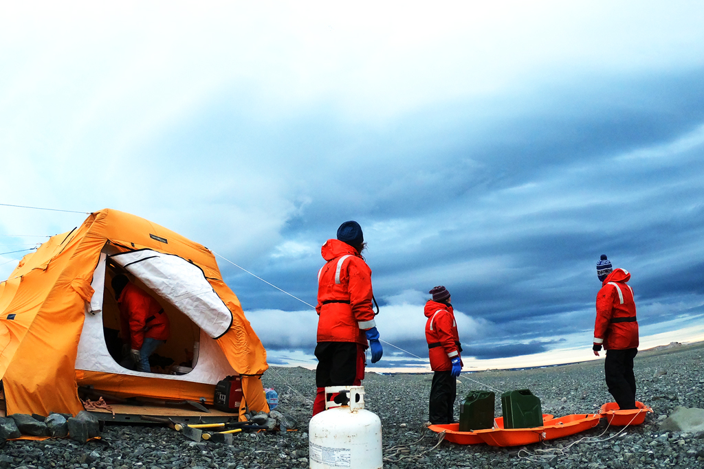 The team pauses while setting up camp to watch the clouds roll in over Joinville Island.