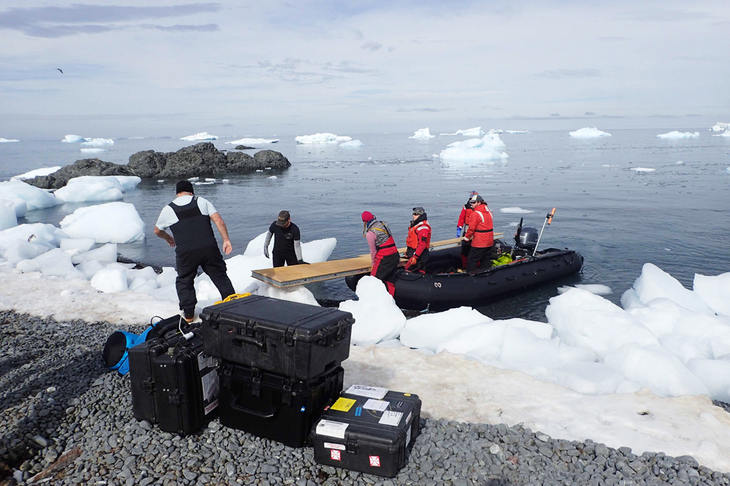 Members of the team lift tent platforms out of the the zodiac.