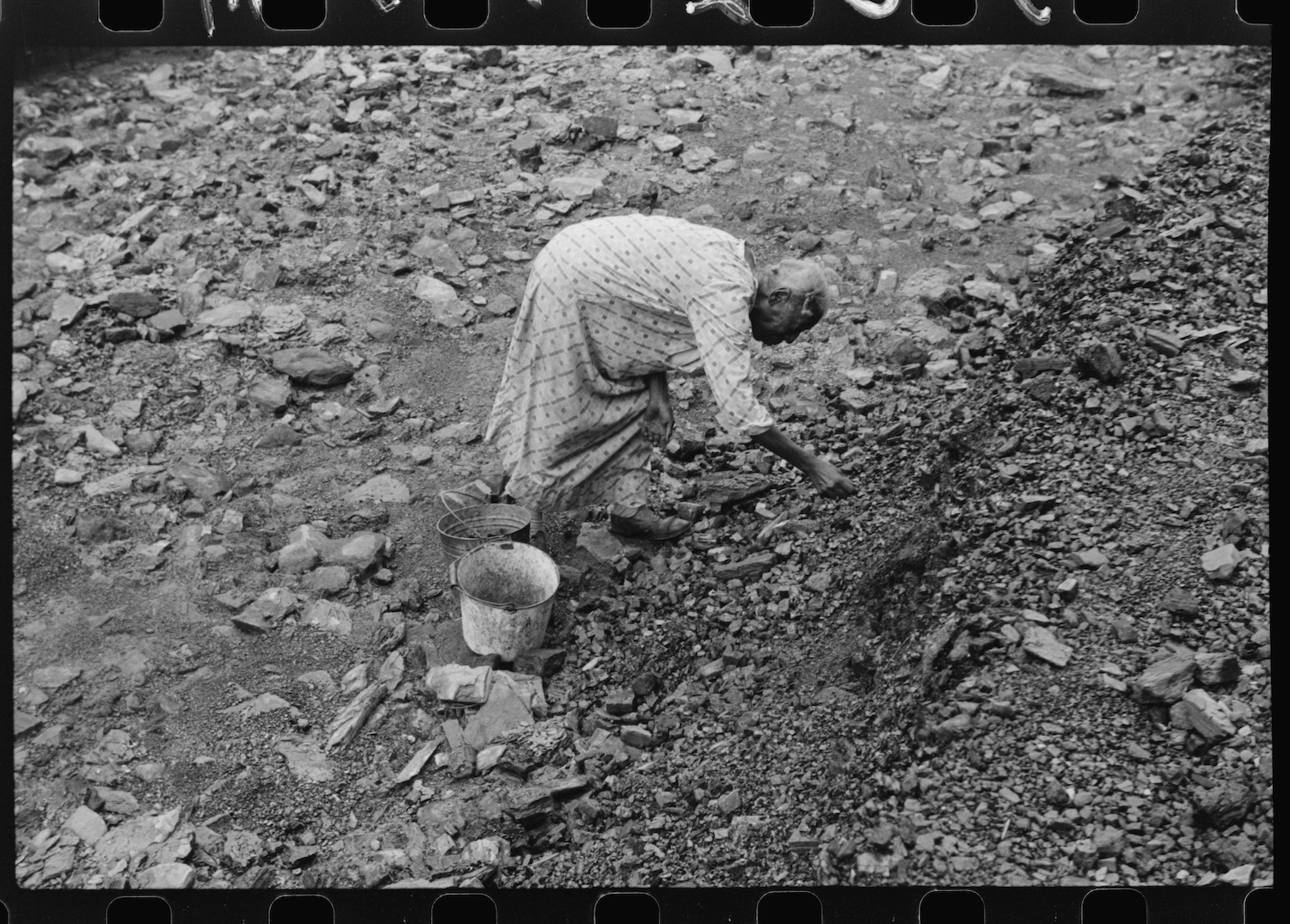 "Negro woman picking up coal from old slate heaps in mining community. The ""Patch,"" Cassville, West Virginia. Marion Post Wolcott, September 1938, Farm Security Administration - Office of War Information Photograph Collection (Library of Congress)."
