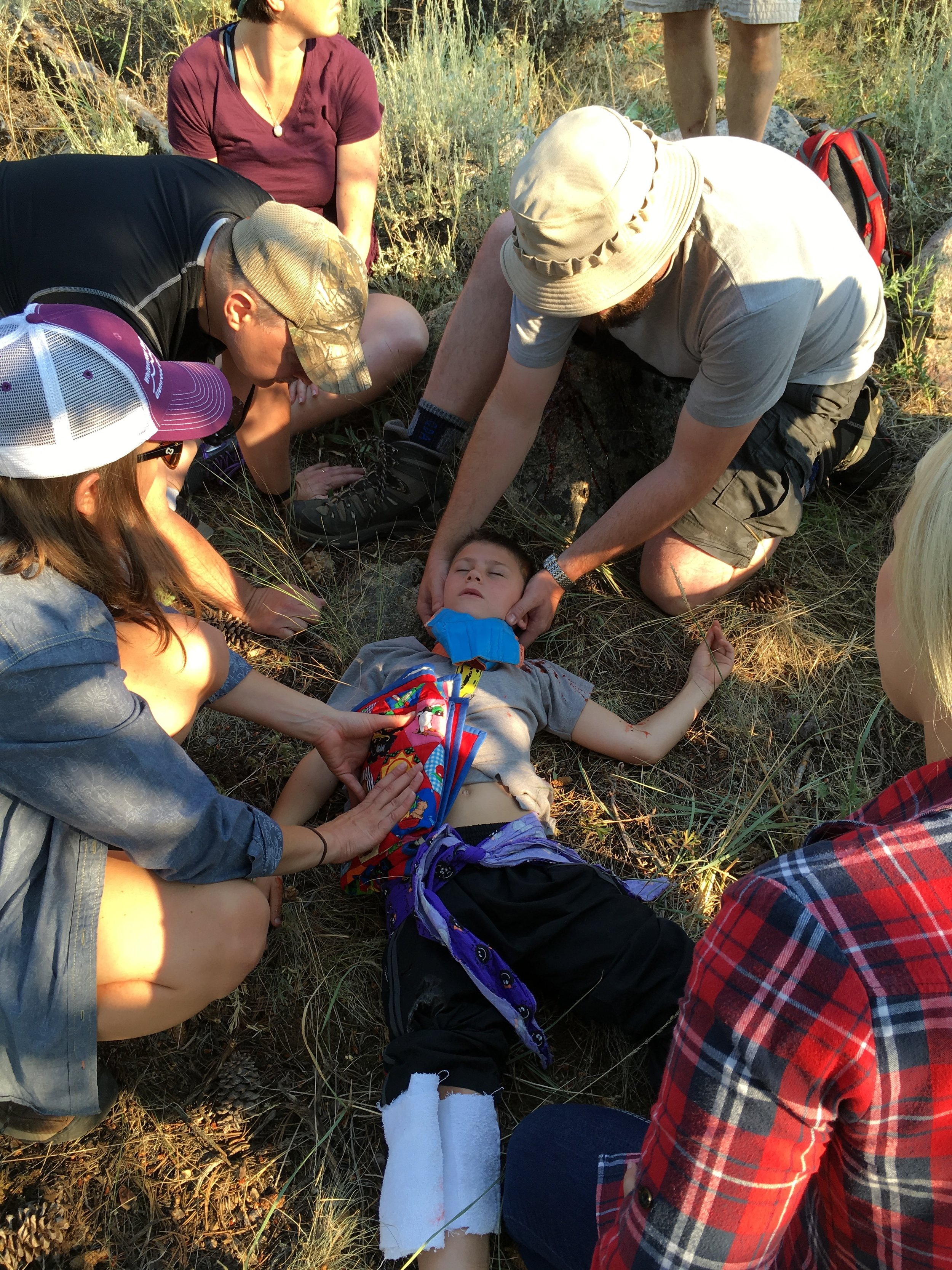 AWLS Students assess a pediatric trauma patient in a field scenario.
