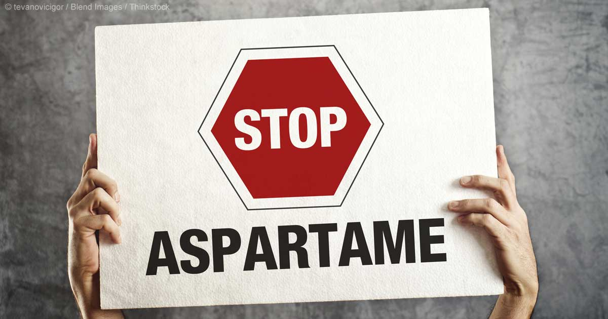 """A pair of hands holding a sign that reads """"Stop Aspartame"""""""