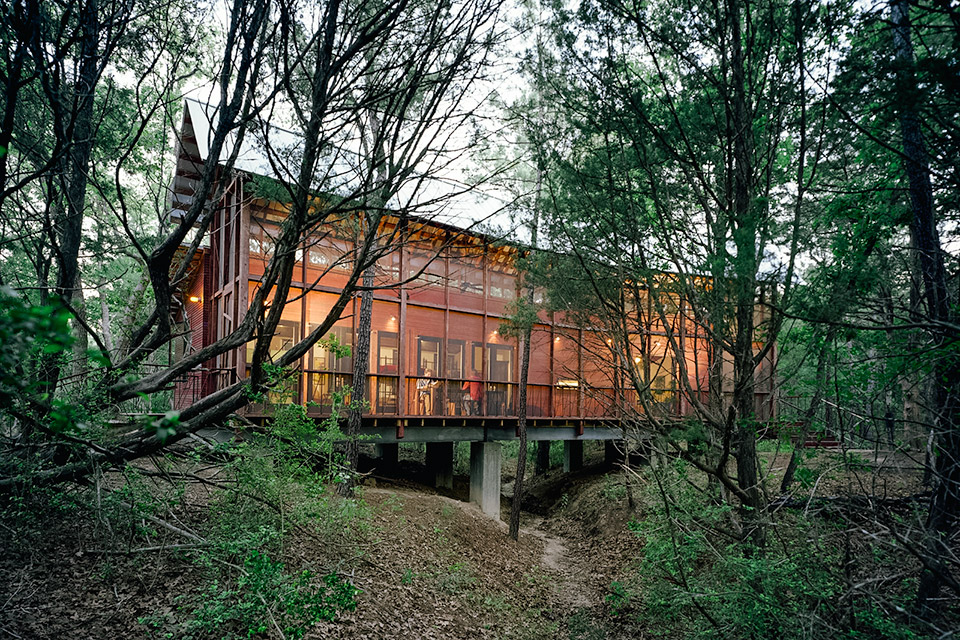 TEXAS BUNKHOUSE  Built as a getaway for a writer/director and his friends and family, this Texas Bunkhouse bends around the trees that dominated its plot, roughly 30 miles from Austin. As the trees dictated the home's shape, so too did they influence its vertically-oriented structure, with the full-length screened porch providing uninhibited views of the surrounding foliage. Inside there are open cots and a kitchen, as well as a single enclosed bedroom, two bathrooms, and an outdoor shower. The building is clad in multi-color stained cedar to blend into the landscape while lending a brick-like randomness, and the house sits on concrete piers above a dry creek bed, just steps from a nearby swimming pool.  Photo: Panton Architect