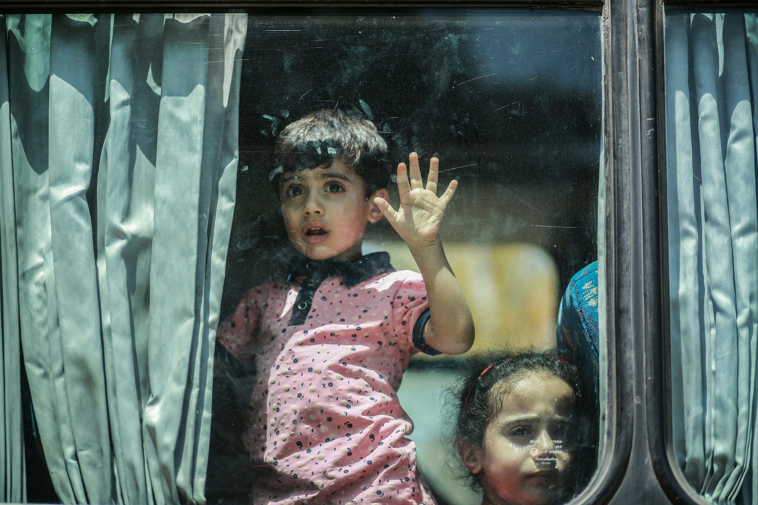 A boy looks out of the window in fear, on the way to the Egyptian border. (Photo credit: Hosam Salim via We Are Not Numbers)