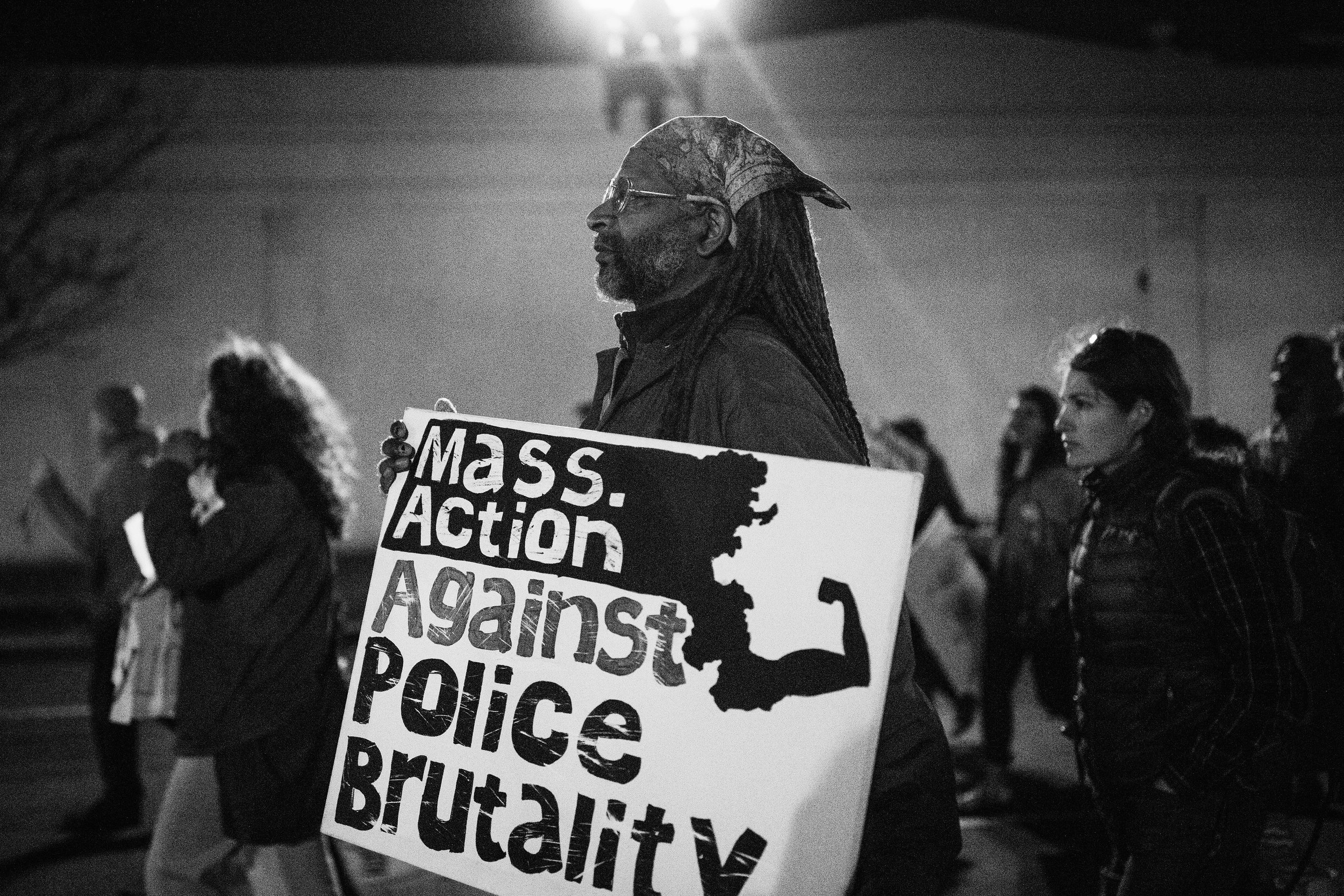 Photo description: A demonstrator marches holding a 'Mass Action Against Brutality' sign. MAAPB organized a Not1More Rally Against Police Brutality at the Boston Police Headquarters in Roxbury on April 4, 2018. (Credit: Emily Goldhammer)