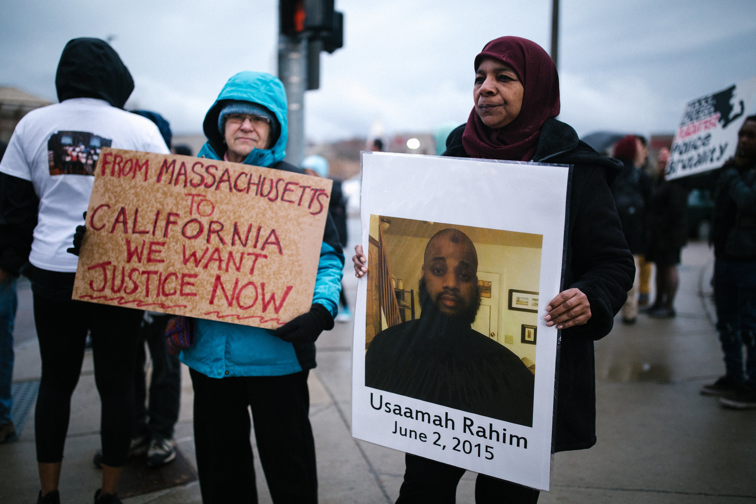 Photo description: Rahima Rahim, pictured on the right, holds a sign with the picture of her son Usaamah Rahim and the date June 2, 2015, when he was killed by Boston police and FBI in Roslindale. To the left, an unidentified protester holds a sign that says 'From Massachusetts to California We Want Justice Now.' (Credit: Emily Goldhammer)