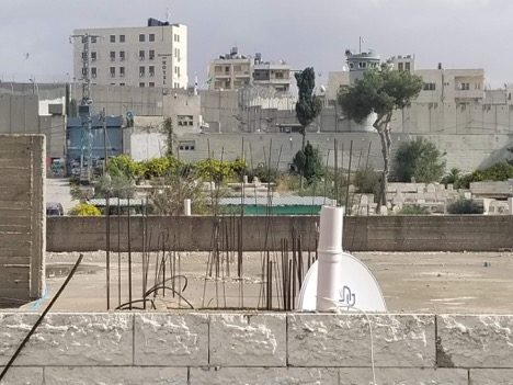 The view from a rooftop in Aida Refugee Camp. The blue gate on the left can be pulled up so that Israeli forces can roll tanks into the camp at any time. (Photo by Charlie Finn)