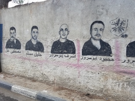 The faces of Palestinian men painted on the walls of the camp. These paintings are in memory of men who have been sentenced to life in Israeli prisons. (Photo by Charlie Finn)