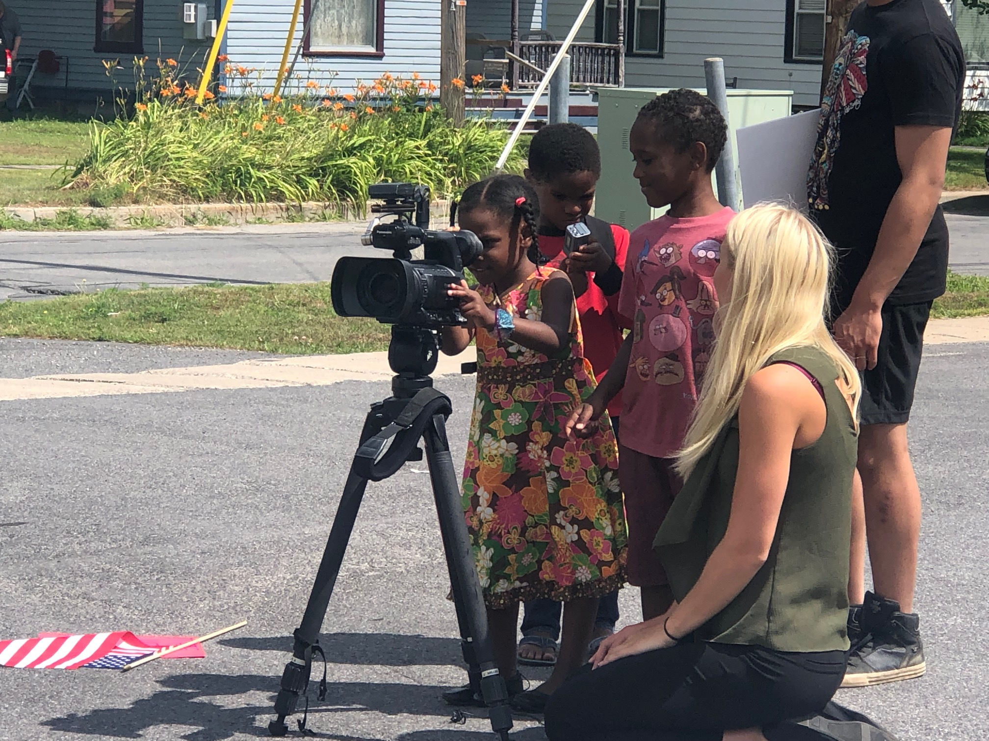 Sarah Evans, Noah Evans (center), and Tre-saiah Evans, march organizer Jennifer Baxtron's grandchildren, take a look through a news camera with WWNY's Emily Griffin, who was reporting on the march in Potsdam.