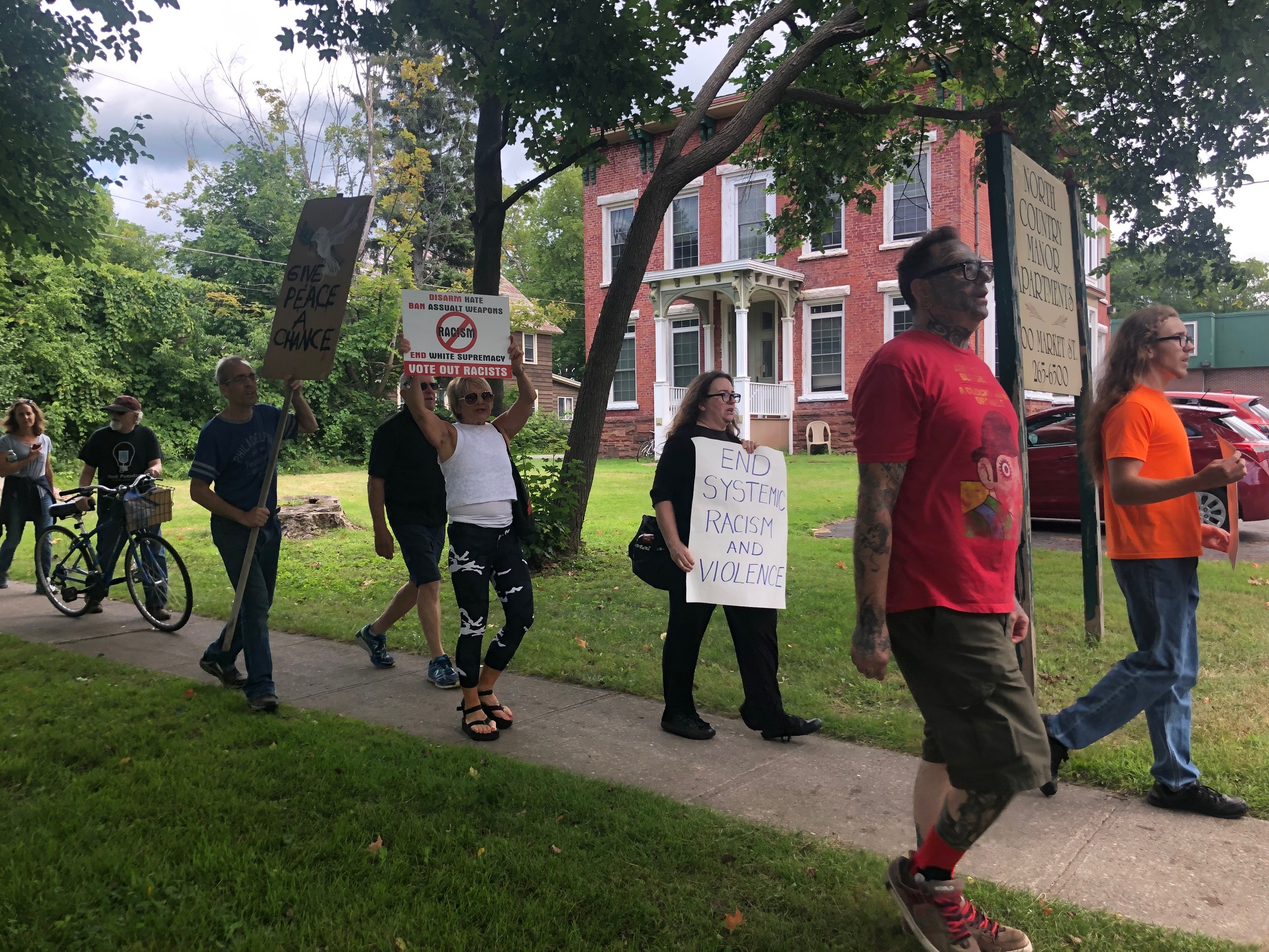 """Demonstrators in Potsdam's """"March against Racism"""" pass 100 Market St., the former home of Garrett Phillips, whose 2011 murder—and the subsequent trial of Oral """"Nick"""" Hillary as the prime suspect—intensified racial tensions in the majority-white community."""