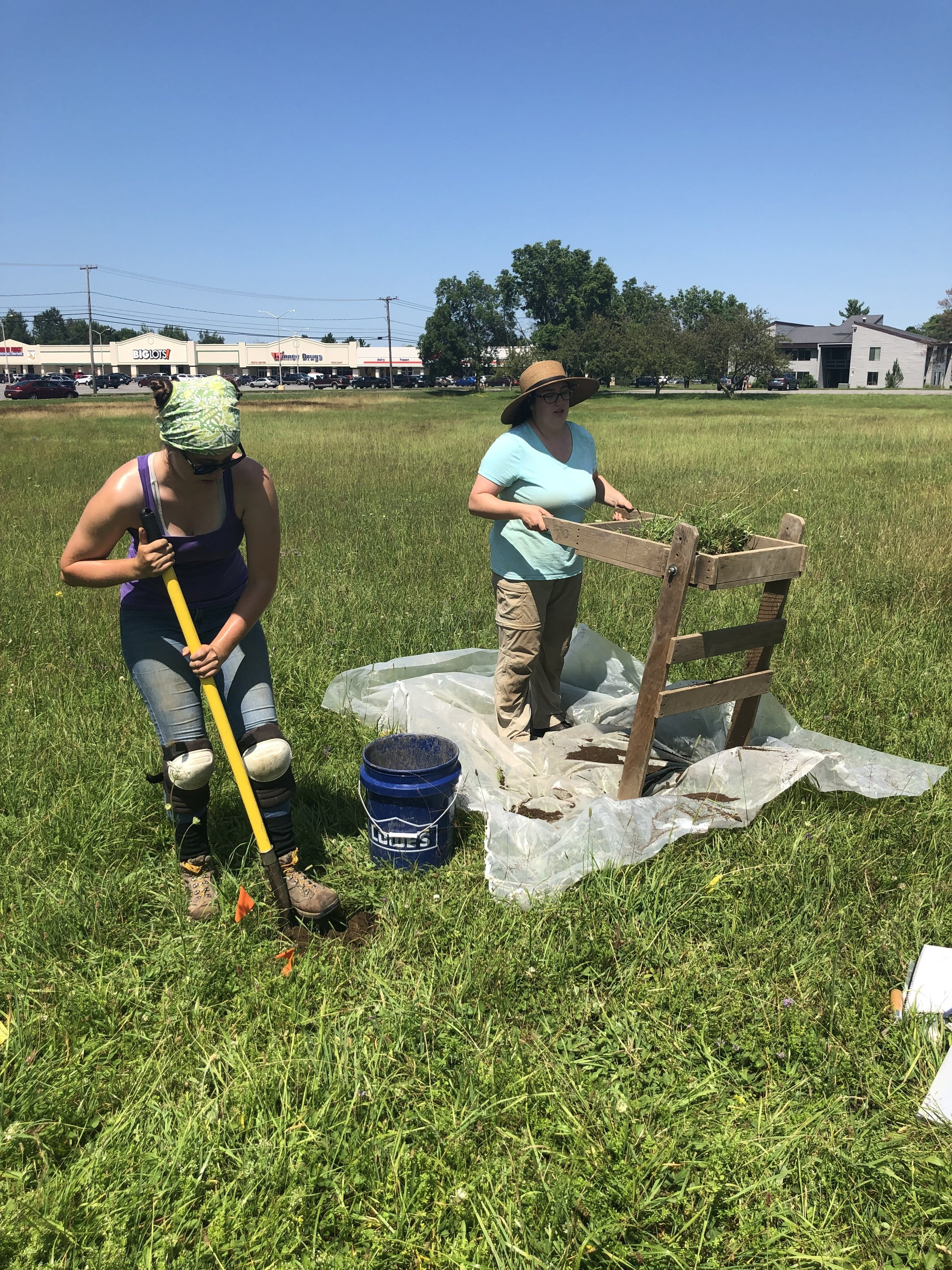 Catt Gagnon (left) and Emily Cox (right), SUNY Potsdam juniors, dig and screen shovel test pits, a standard method of archaeological surveying. (Photo credit: Nicole Roché)