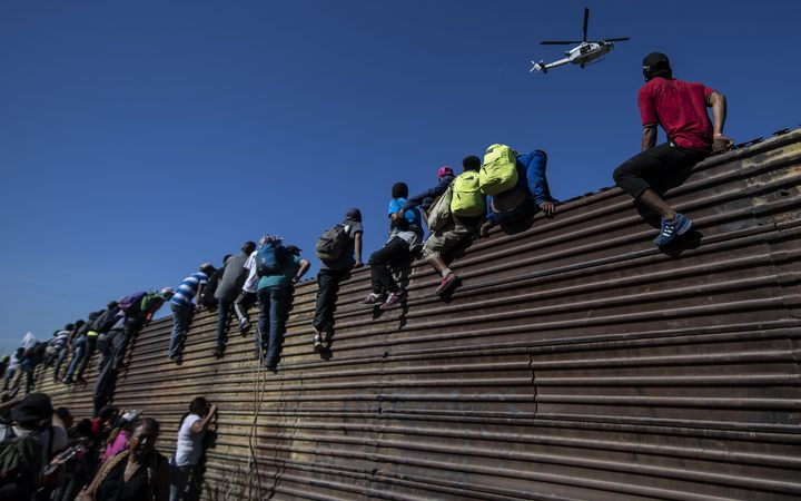 Migrants climb across walls and other barricades in an attempt to enter the US