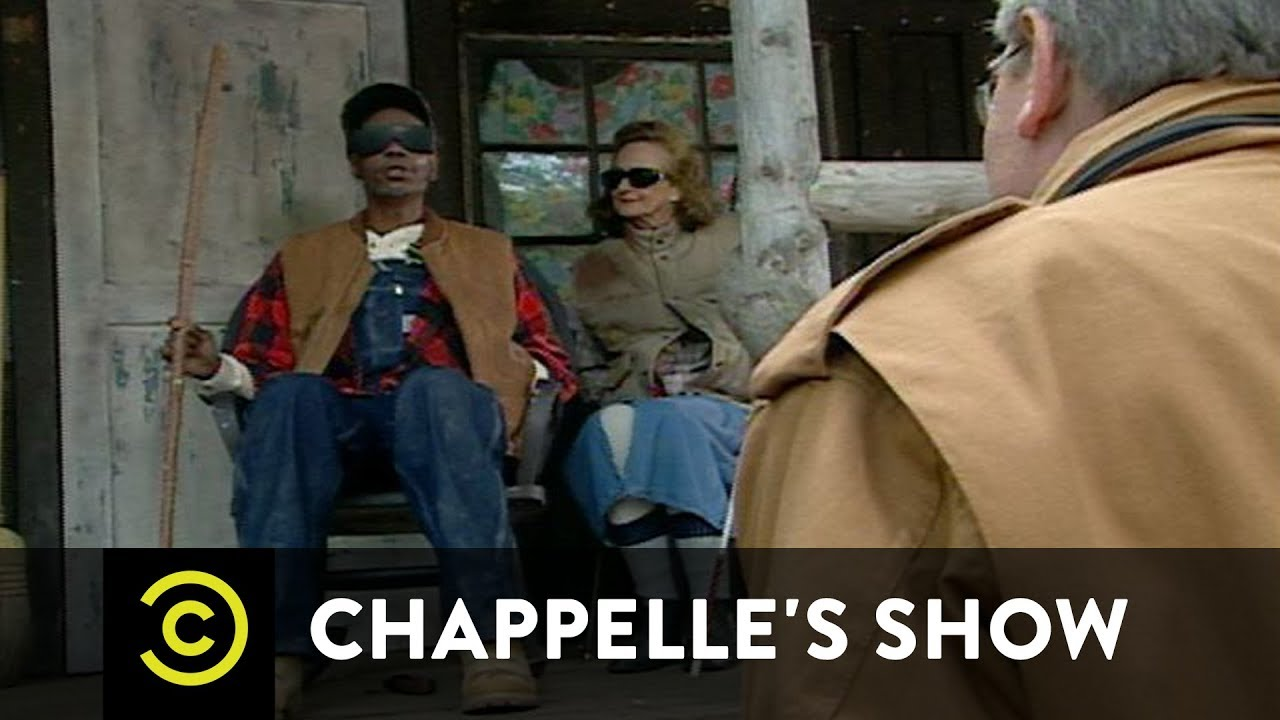 """A scene from Comedy Central's  Chappelle's Show,  featuring Dave Chappelle as white supremacist Clayton Bigsby on the left; SPOILER ALERT: the show ends after Bigsby is informed of his race, and answers the interviewer when asked why he divorced his wife of many years: """"she was a n*gger lover"""""""