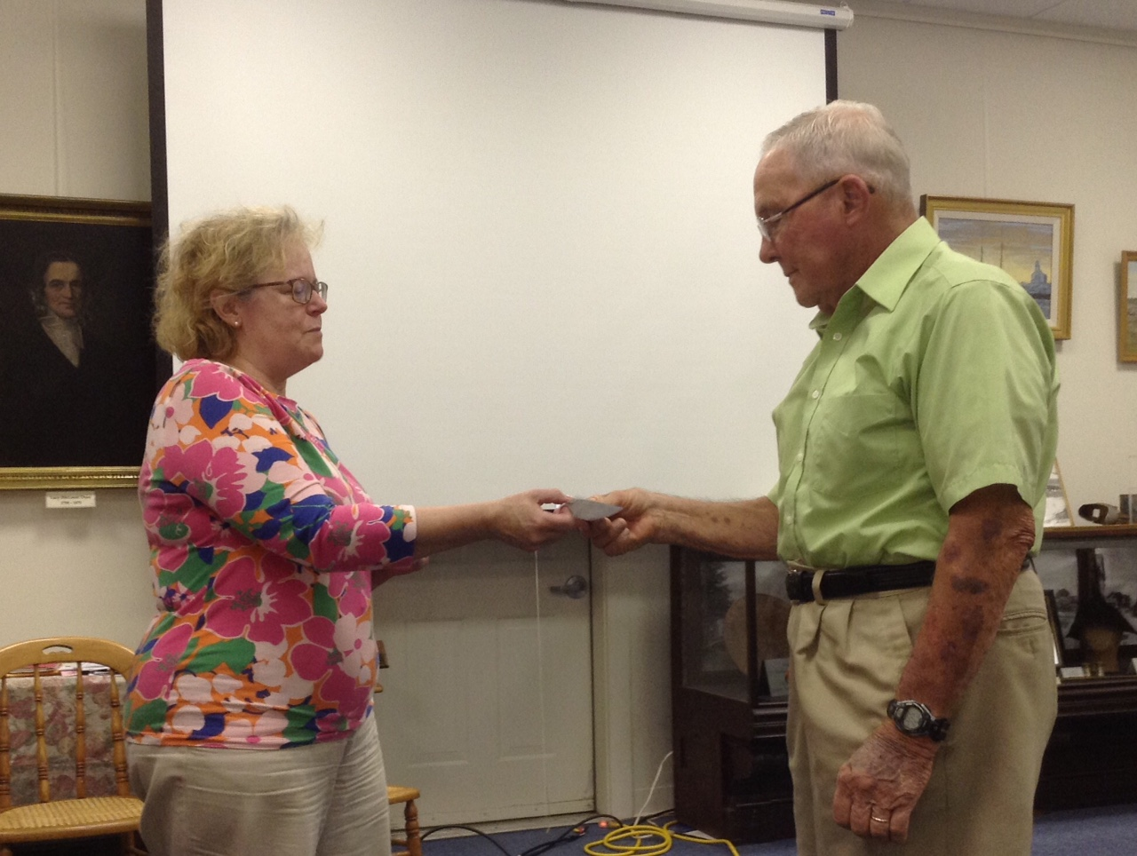 Ann Smith, treasurer of the Wessaweskeag Historical Society, hands the donation to Peter Markoon of the People's United Methodist Church.