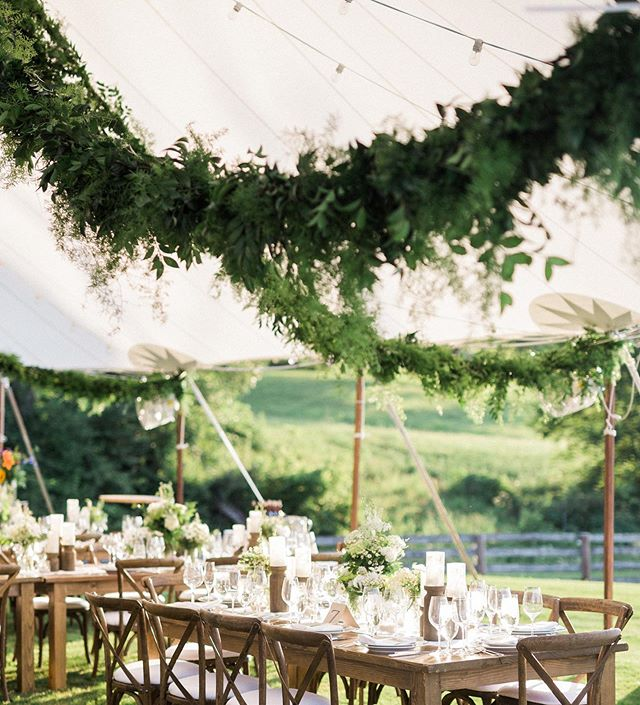 Lush Green garland hangs overhead this dreamy tent. XO Planning Design and Floral @blisschicago  #tentedwedding #tentedevent #chicagoeventplanner #eventdesign