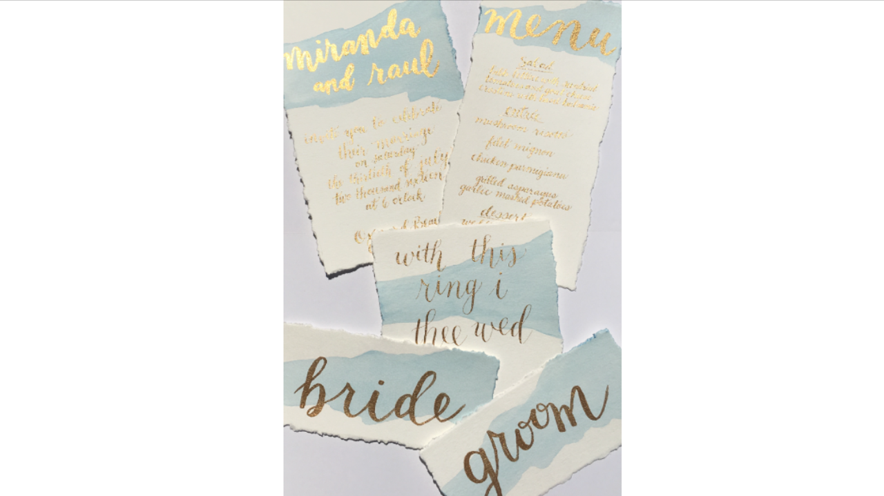 perfect for a beach wedding - a soft blue watercolor wash and gold lettering wedding invite, menu, ring card and place cards for the bride and groom