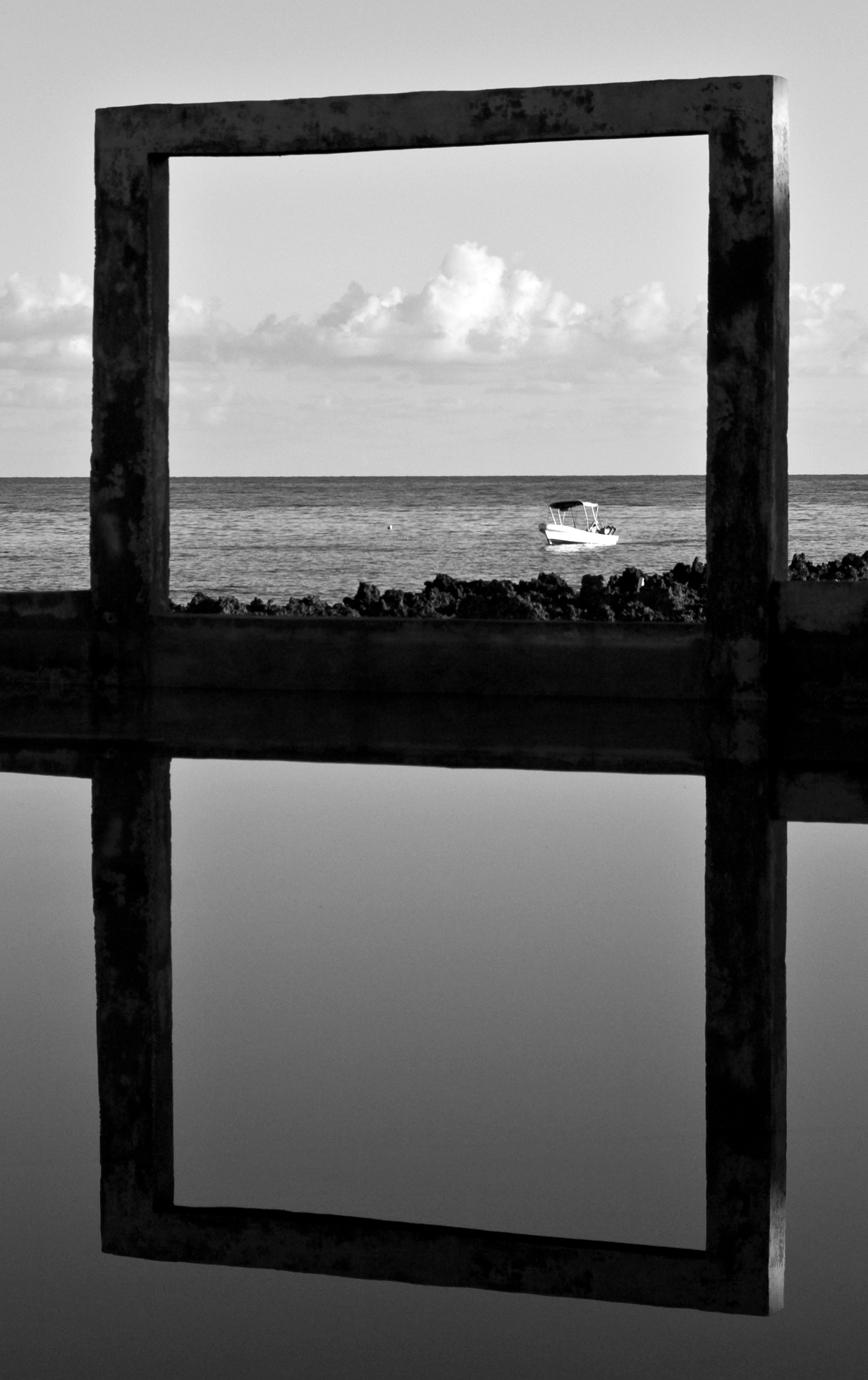 A fishing boat passes behind a concrete frame and swimming pool off the coast of Roatan, Honduras.