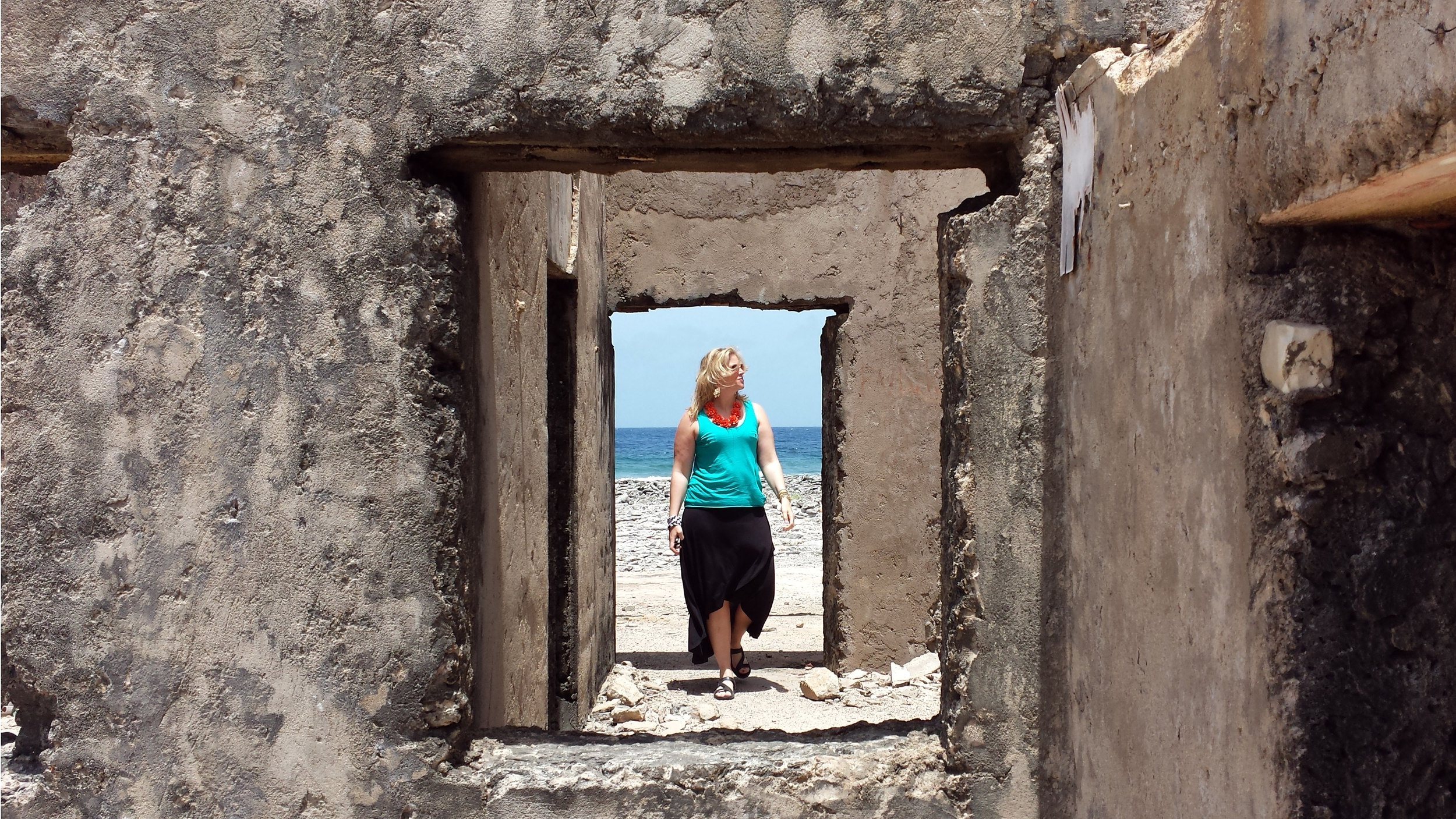 A woman walks through the ruins of a seaside home in Bonaire, an island in the Leeward Antilles.
