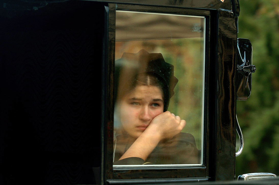 An Amish girl looks through the window of a buggy riding in the funeral procession for four of six Amish girls executed in a one-room schoolhouse in Lancaster County.  Photo credit:  Guy Wathen