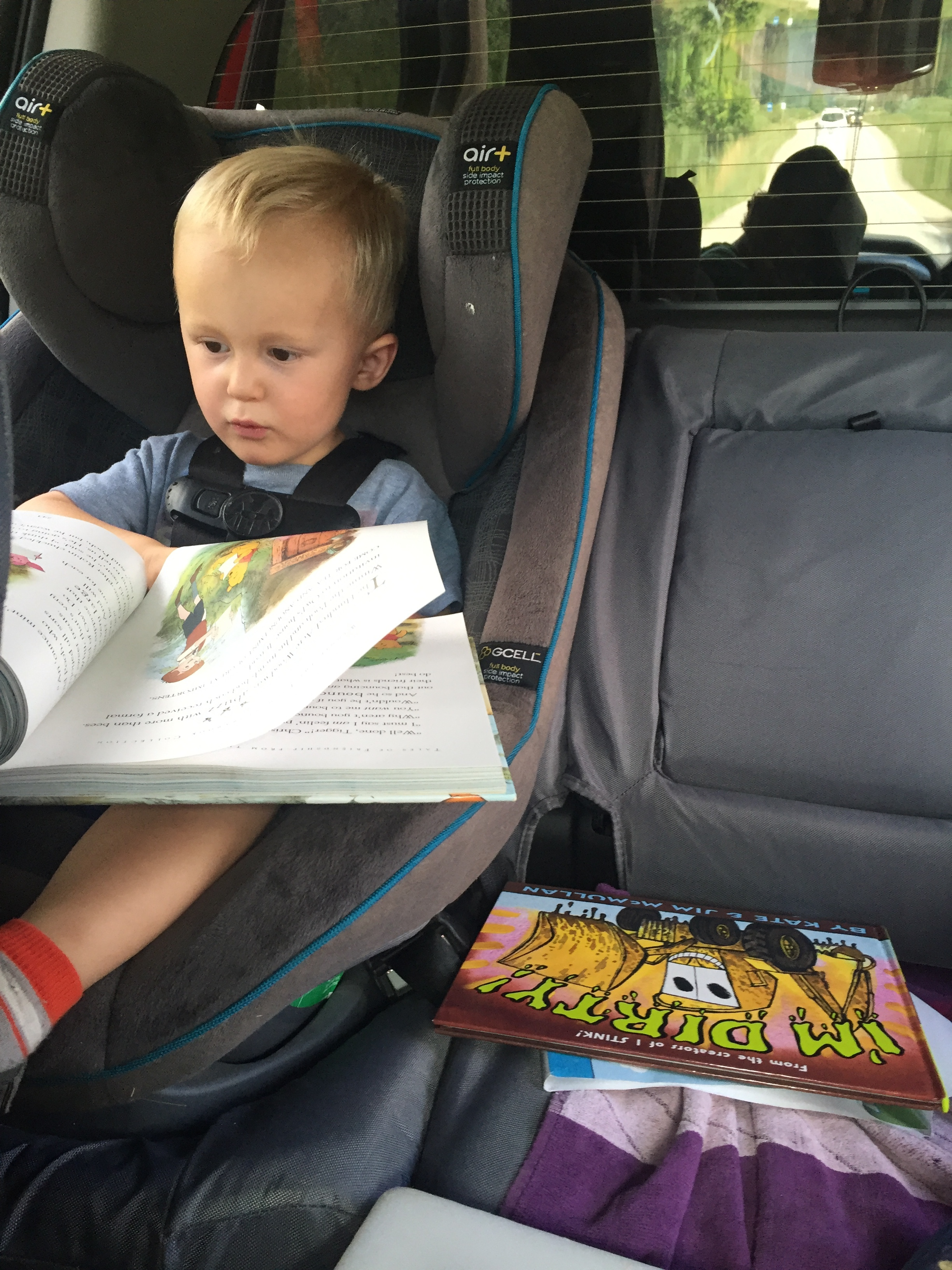 "It is a glorious thing when your toddler begins to ""read"" to himself. Happy, self-entertained traveler! Score!"