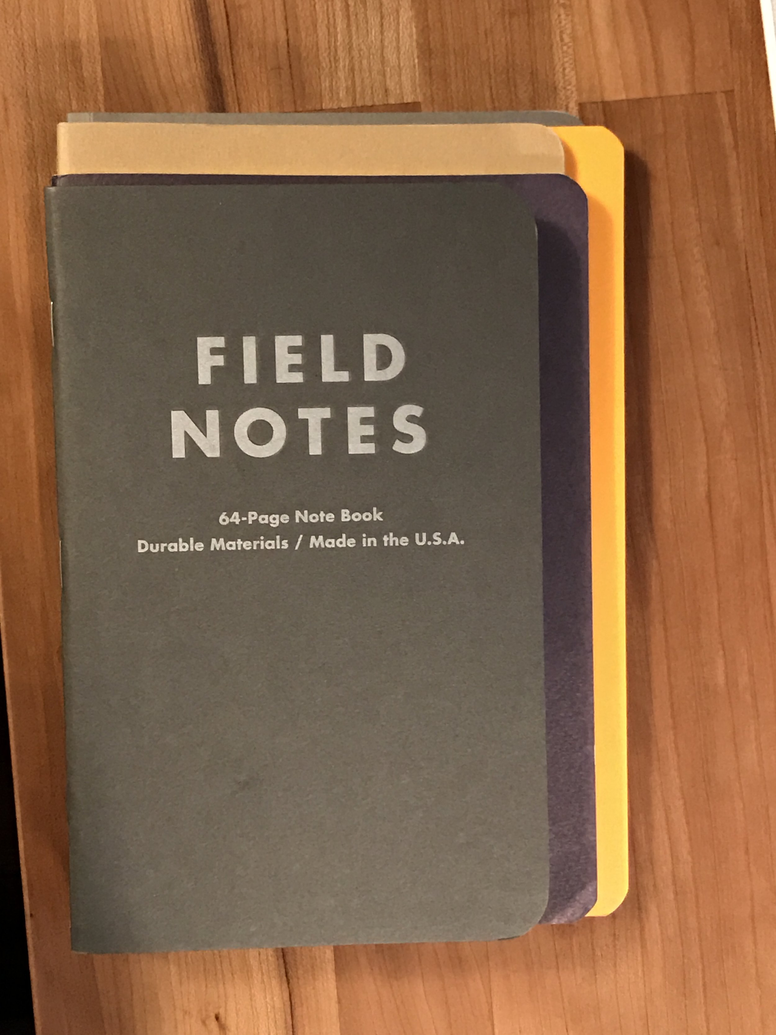 In stack order: Field Notes Arts & Science, Baron Fig Flagship Vanguard, Moleskine Cahier Large, Rhodia Side Staple A5, Write Notepads Paper Journal (barely peeking out the top.)