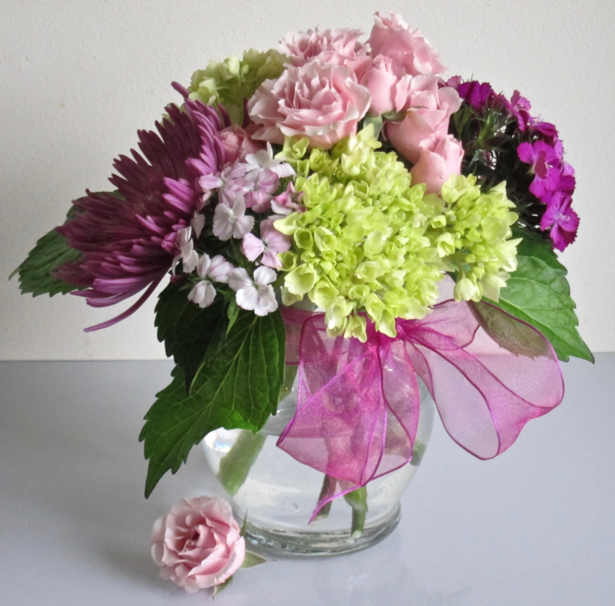 NEAT AND TIDY   A mound of seasonal flowers in a low ginger vase, $40. Cremons, dianthus, mini hydrangea, roses.