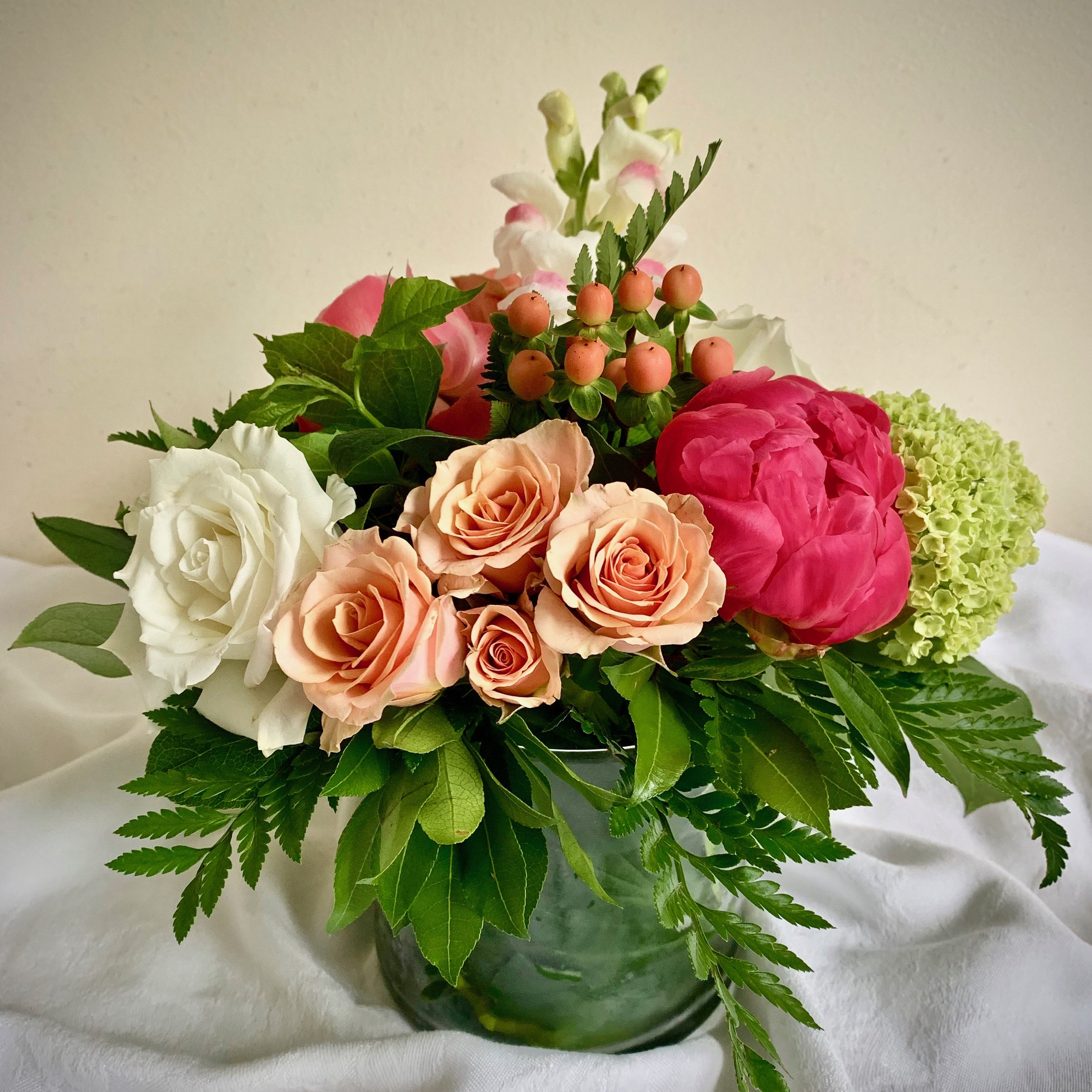 PREMIUM PEONY CENTERPIECE  with lime  hydrangea, spray roses and roses in a leaf-lined vase, $55.