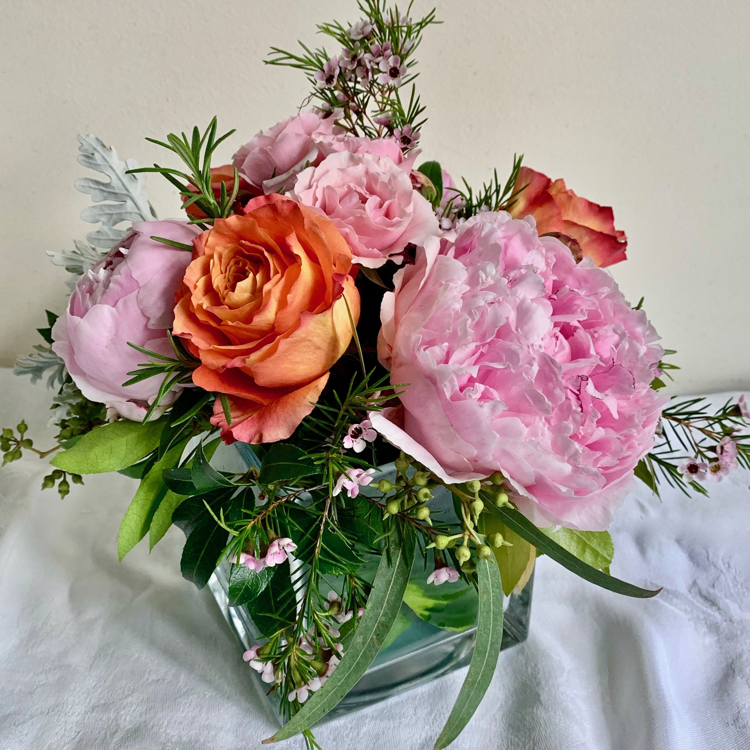 ROSEMARY for Remembrance   with fragrant waxflower, peonies and roses in a leaf-lined glass cube, $60.
