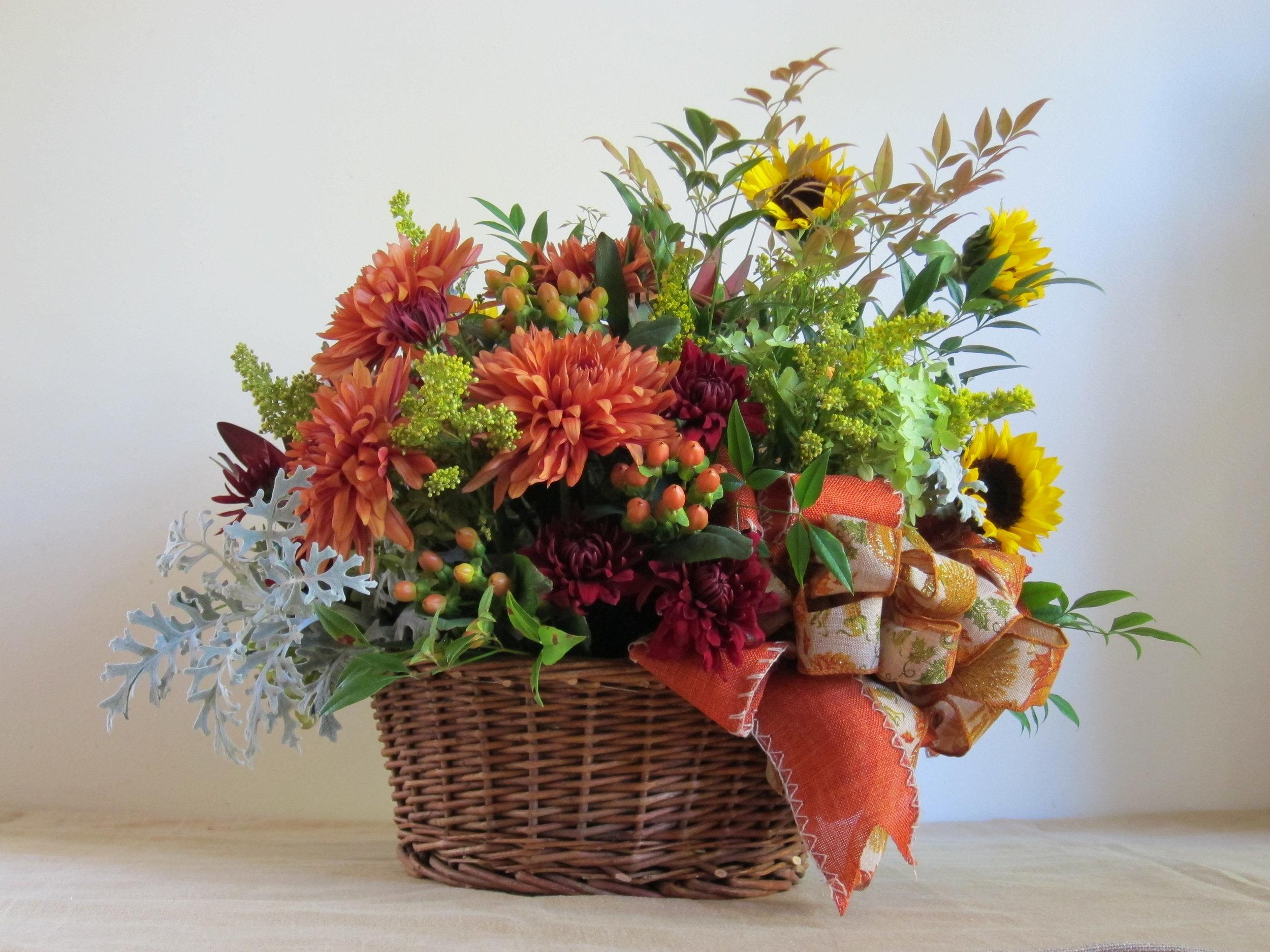 MEDIUM BASKET   of seasonal flowers in a natural wicker basket, $75.